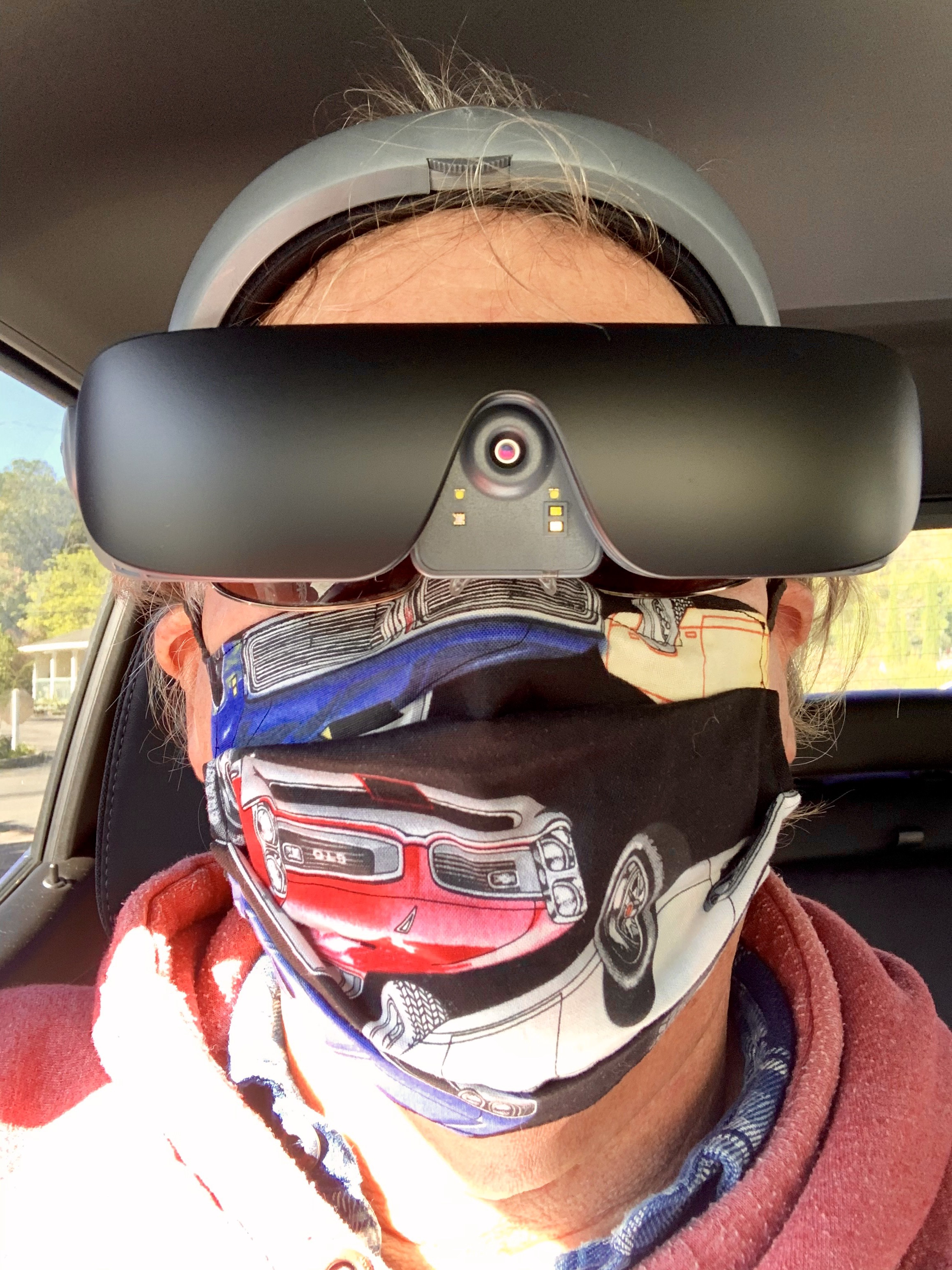 Man looking at the camera wearing a mask and eSight 4 in the down position over prescription sunglasses.