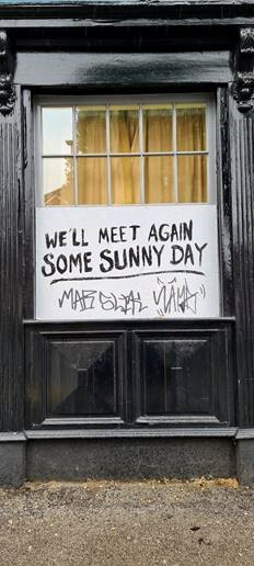 """A sign in a pub window reading """"We'll Meet Again Some Sunny Day"""", with graffiti"""