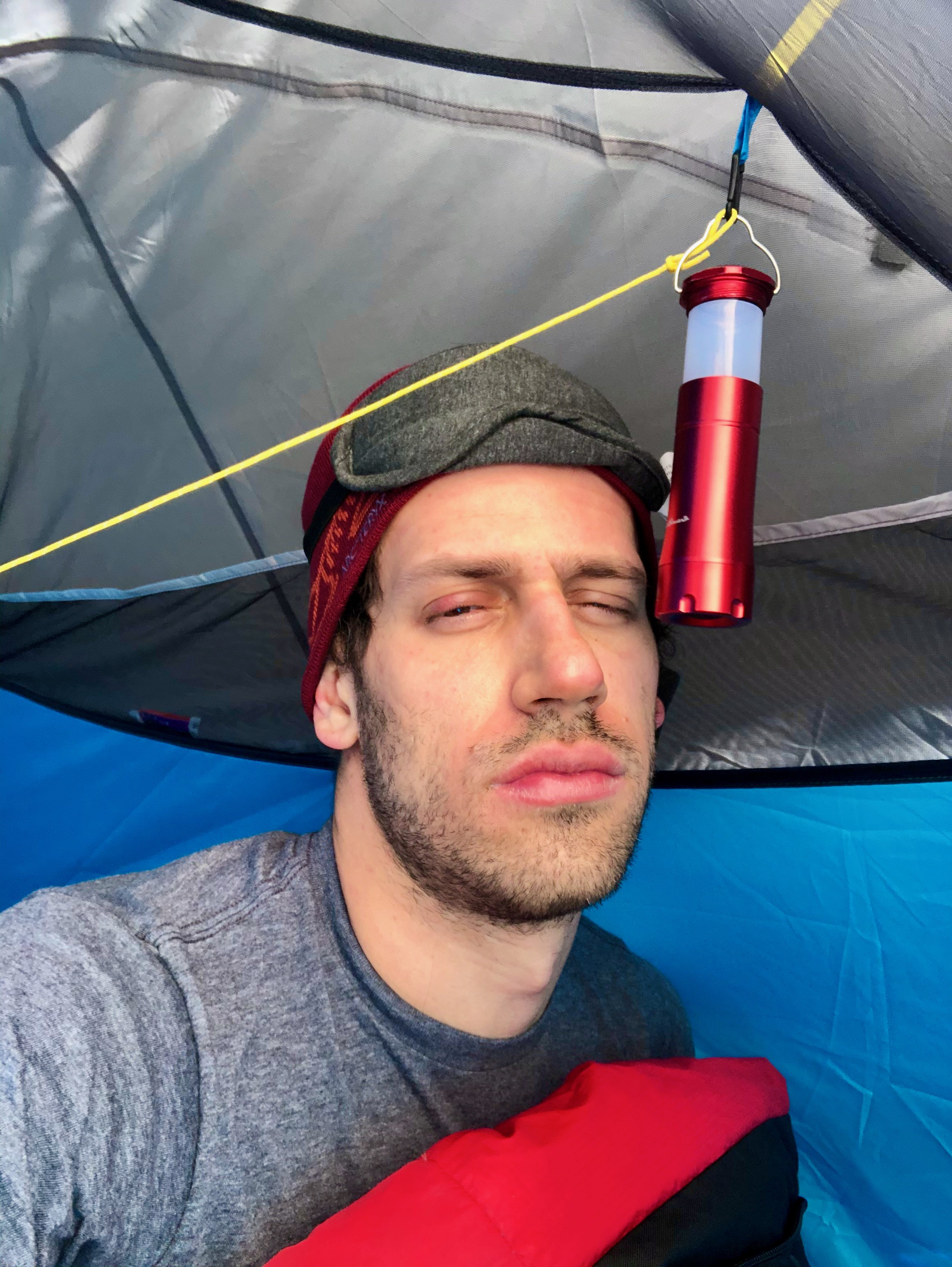 Cameron camping, but looks upset about it.