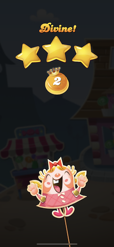 """A candy character wearing a bow celebrates under """"Divine!"""" and three gold stars earned at a level's successful completion."""