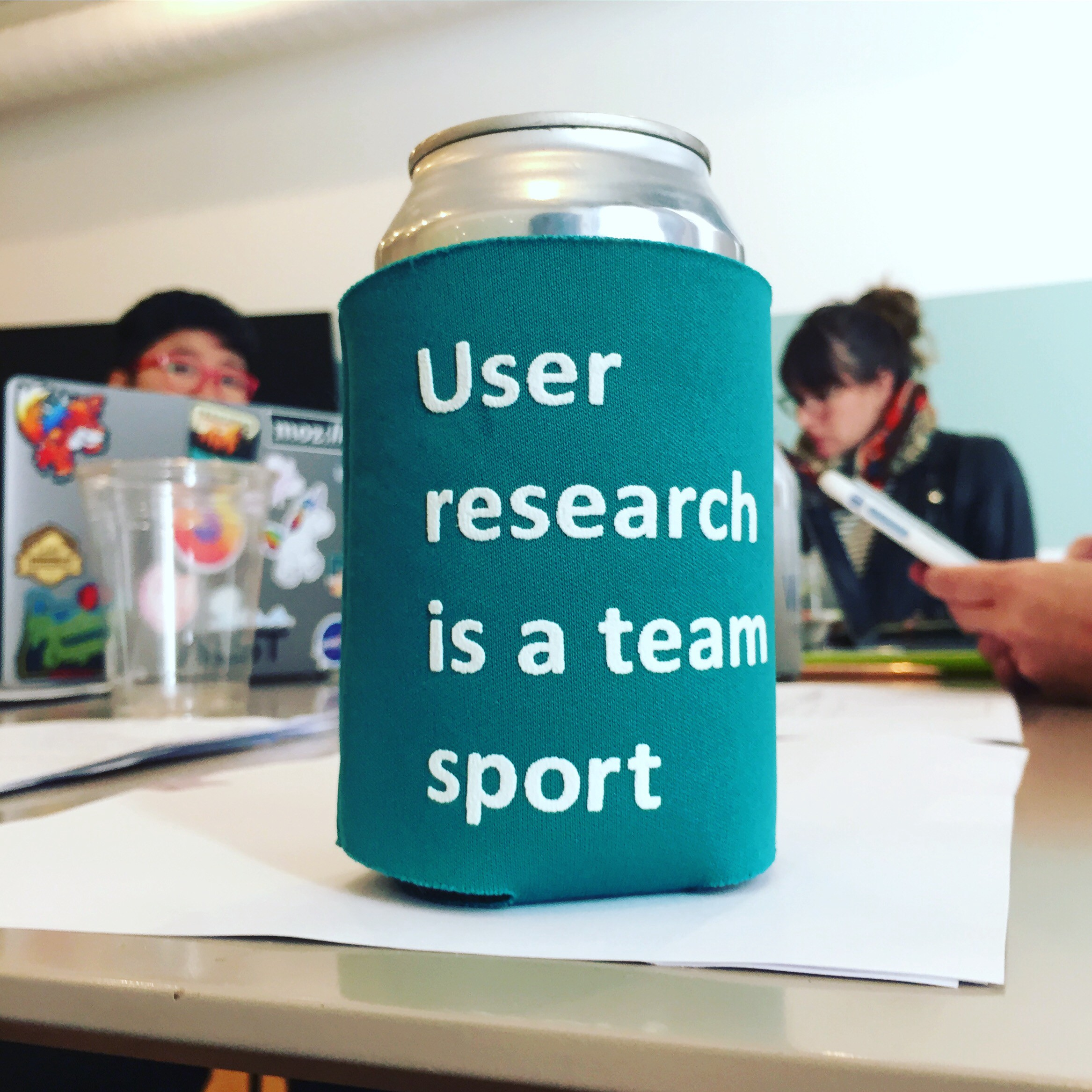 """A soda can in a coozy that says """"User research is a team sport,"""" sitting on a table with people & laptops in the background."""