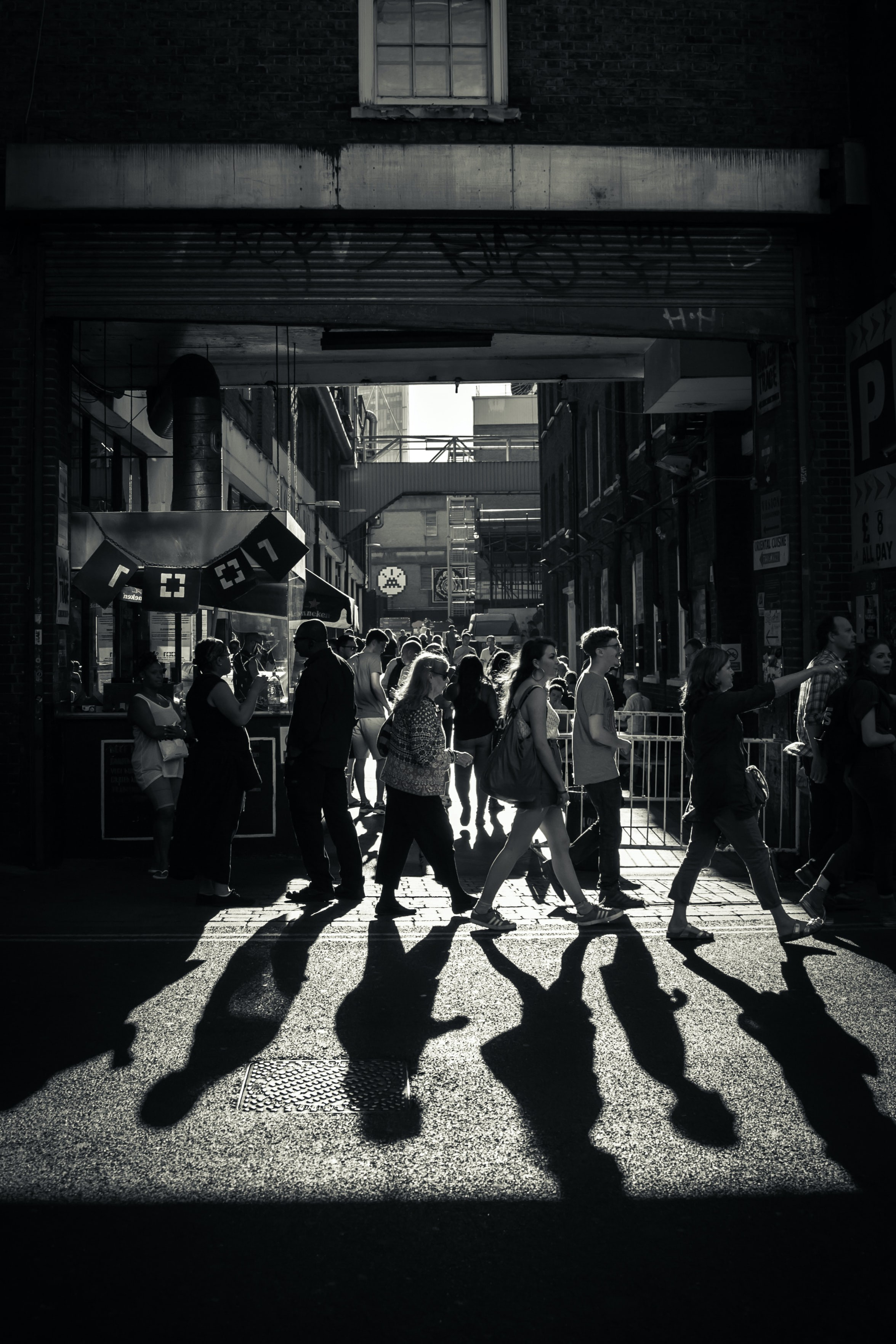 Greyscale photo of a crowd crossing the street.