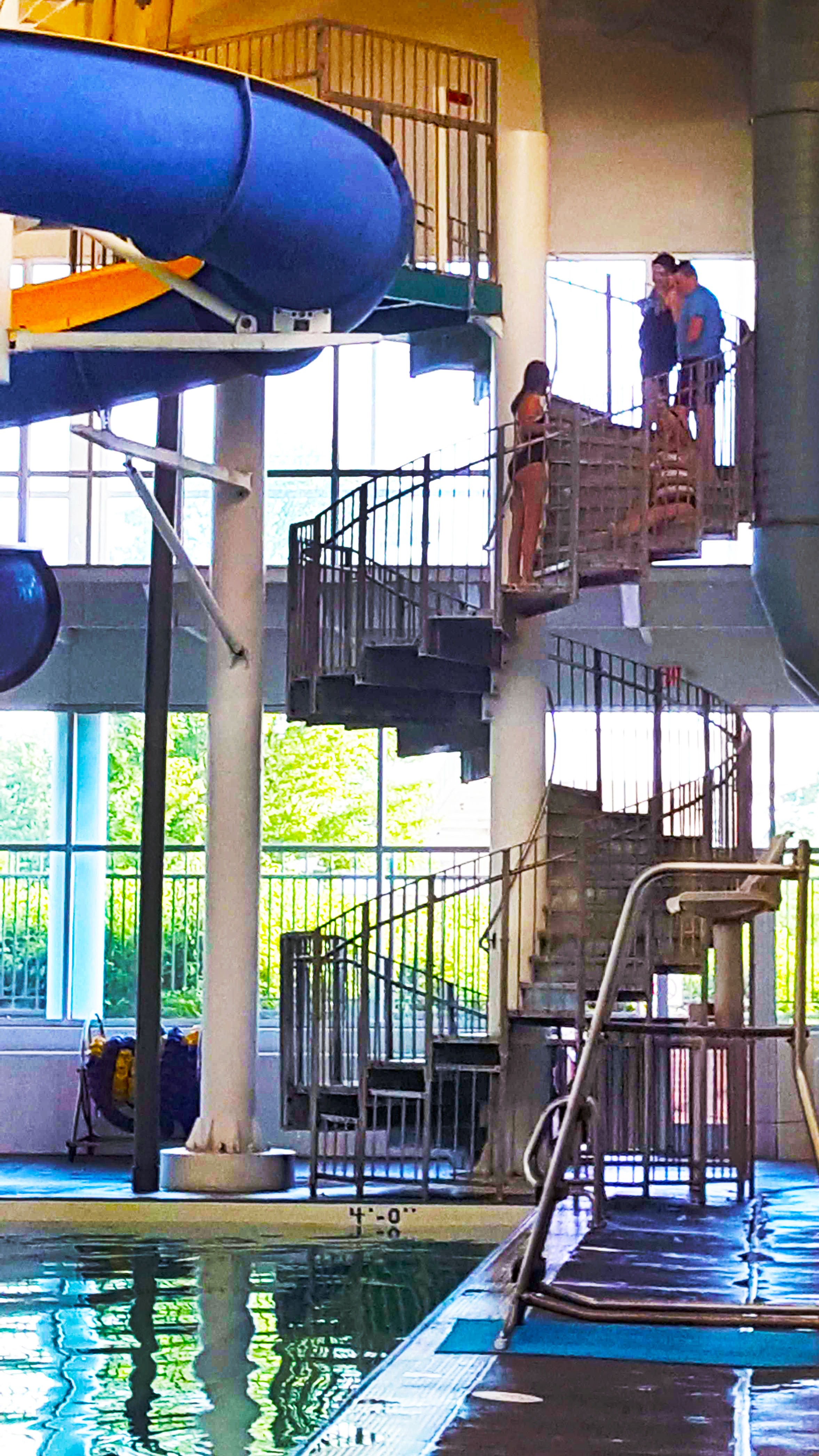 Spiral staircase one story tall leading to a waterslide. Girl is sitting on steps pulling herself up them. 3 friends nearby.