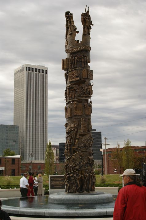 A large towering monument in front of skyscrapers.