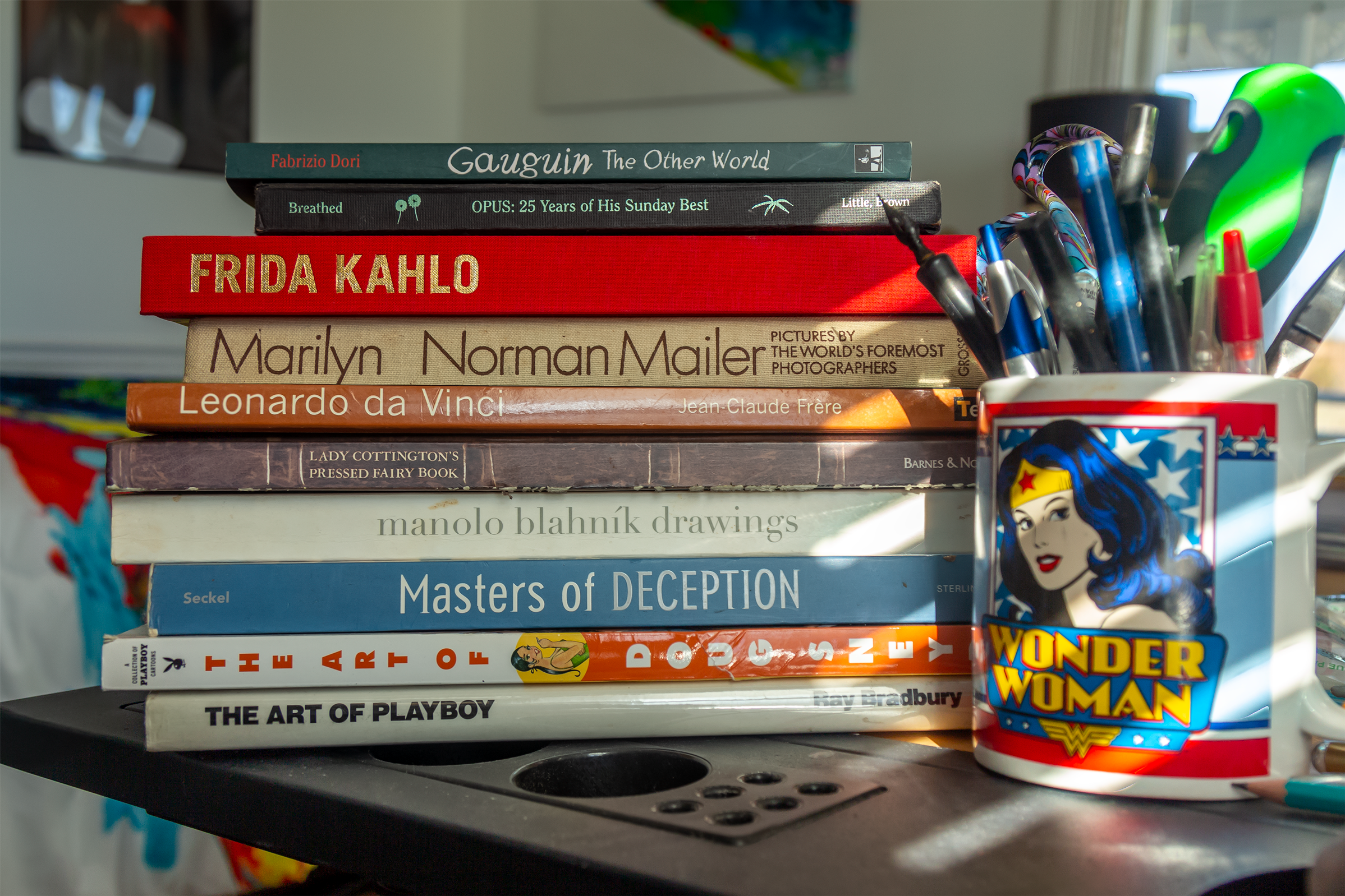 A stack of art books on a drafting table with a Wonder Woman coffee mug full of pens.