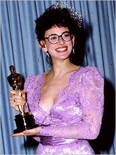 Marlee Matlin holds her Academy Award while wearing a purple dress.