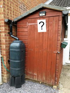 An English back-garden shed, with a question mark on it.