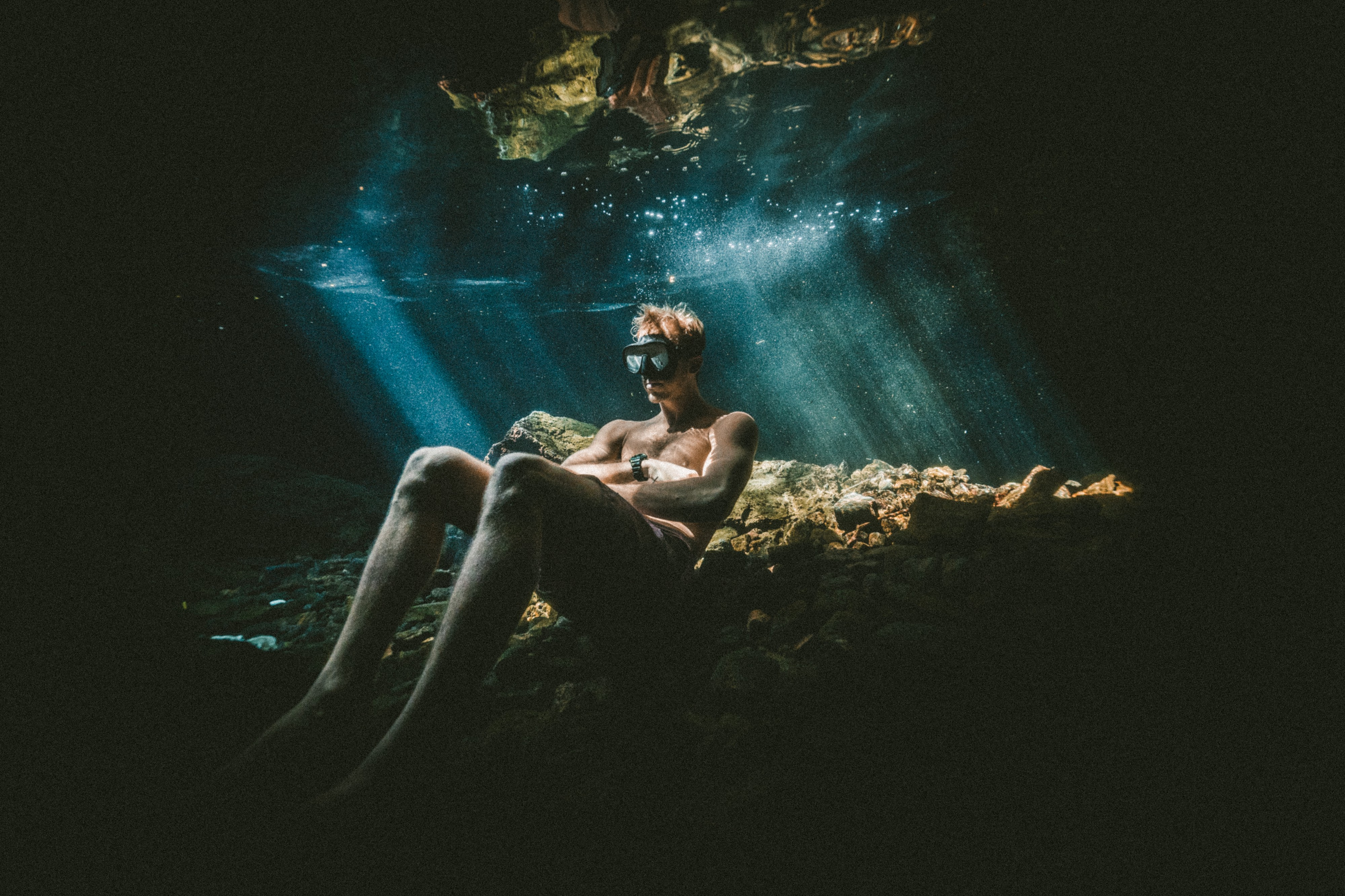 Swimmer sitting on the ocean floor contemplating