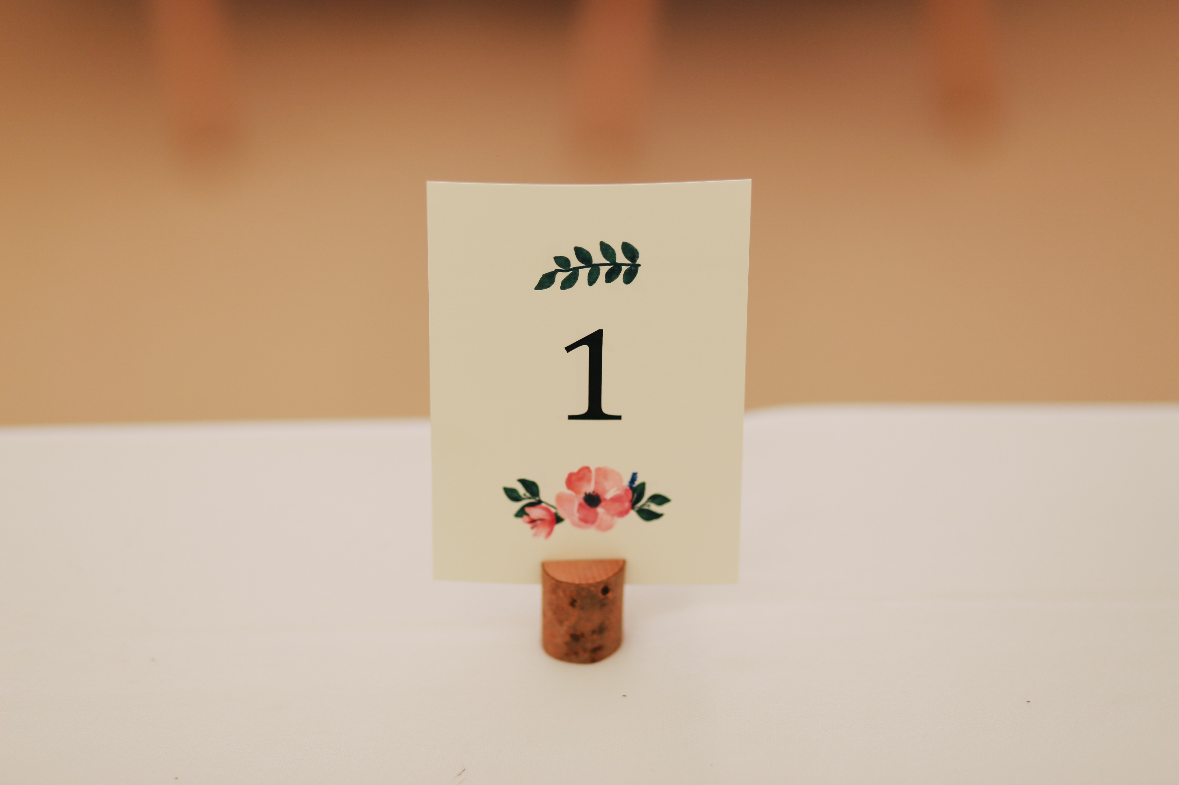 "A placesetting sits on an otherwise empty table. The card simply says ""1""."