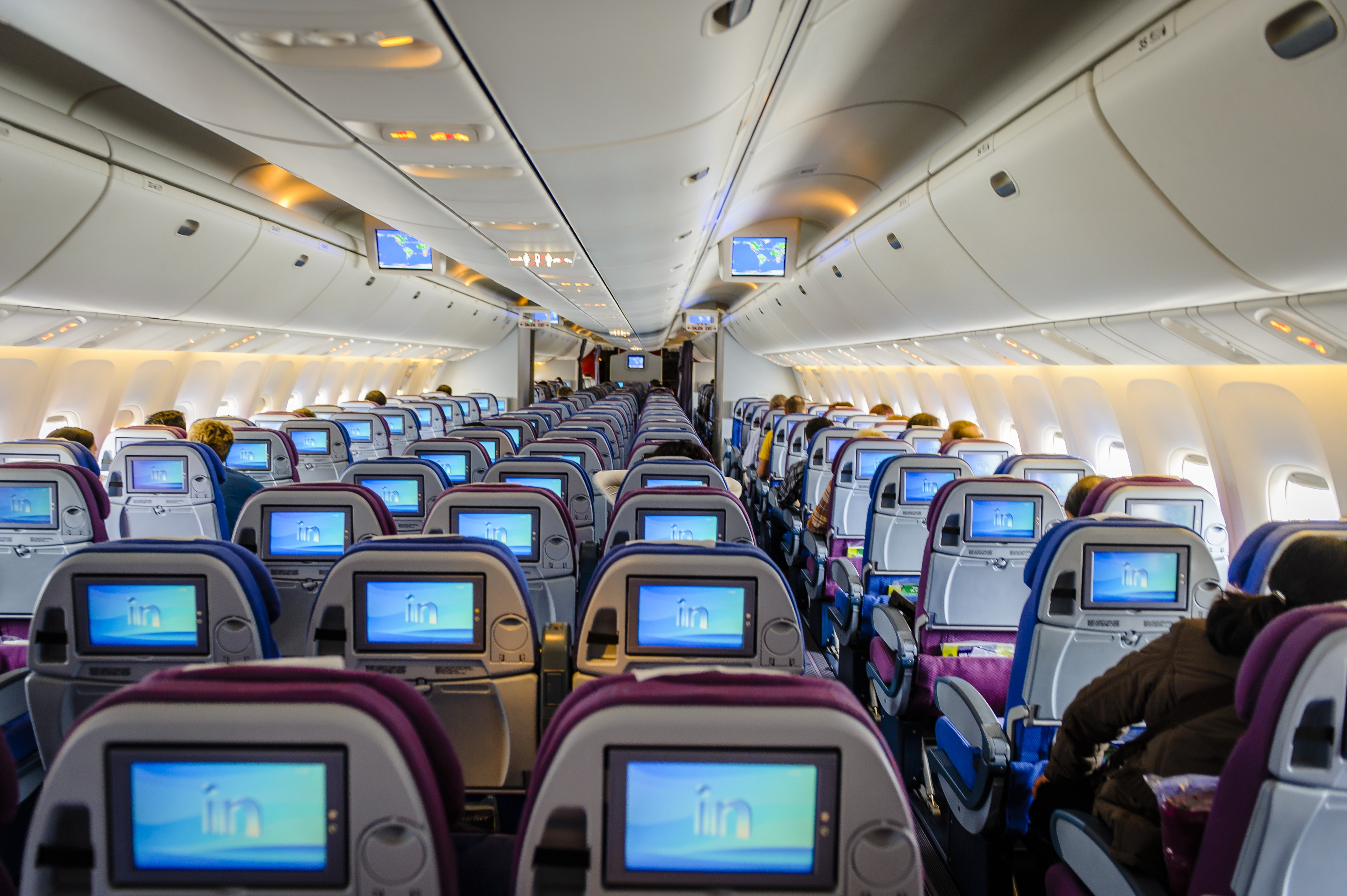 An aircraft cabin with rows of seats, some of which have people sitting in them, watching the T.V. screen on the back of the seat in front.