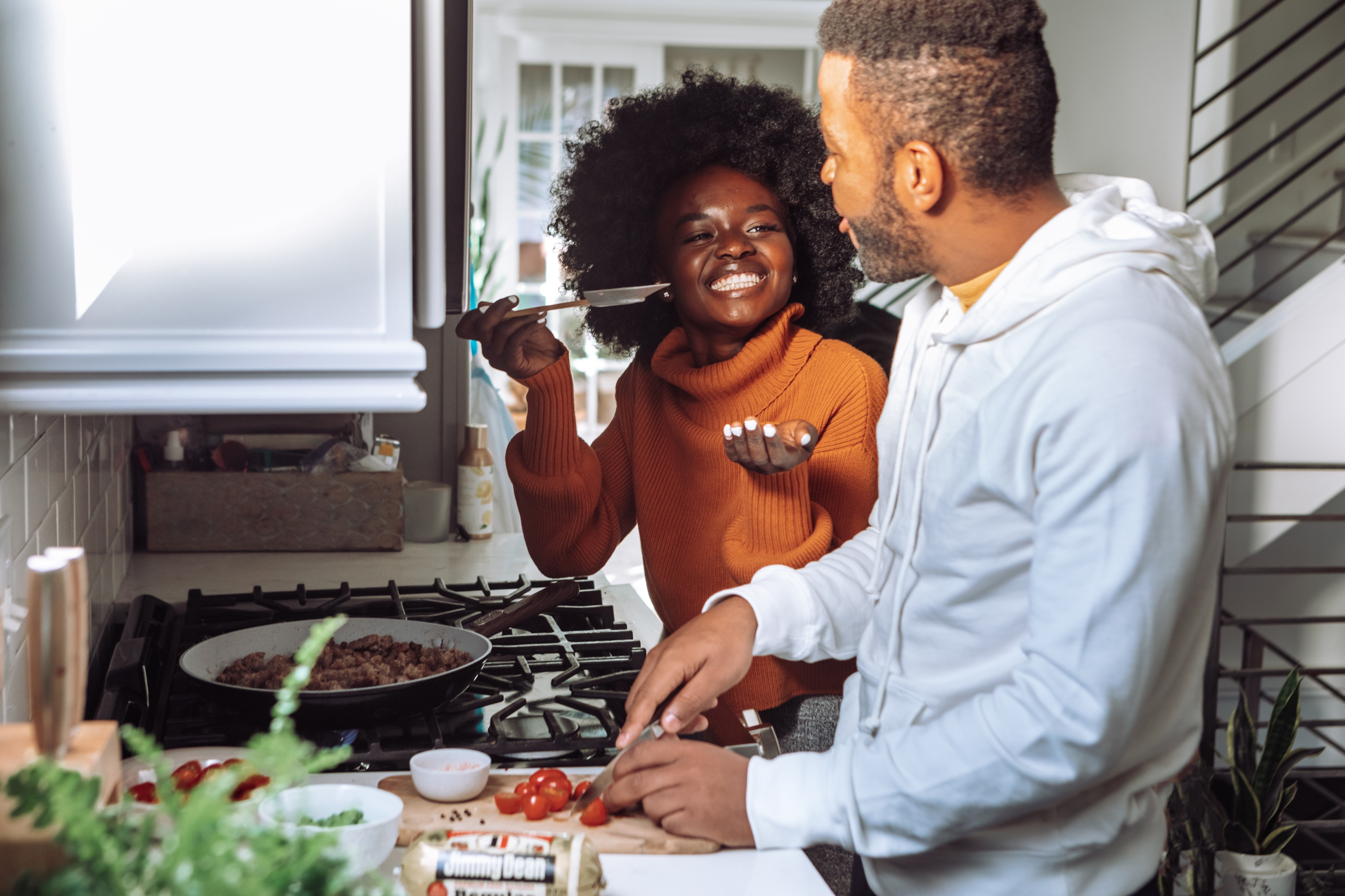 A Black woman in a kitchen with her partner. She is holding up a spoon and grinning widely, as her partner chops up some tomatoes.