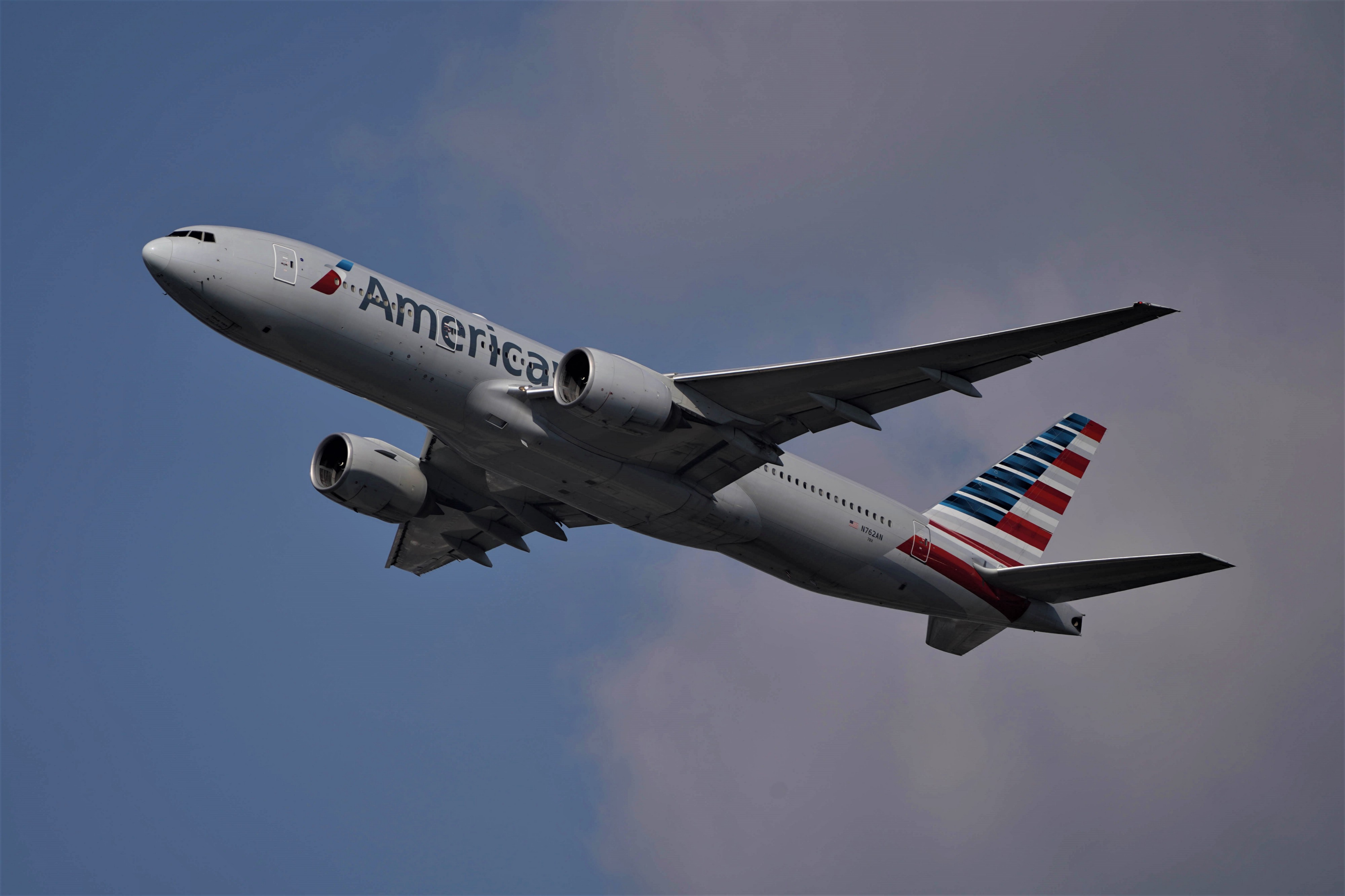 An American Airlines plane is seen flying through the air.