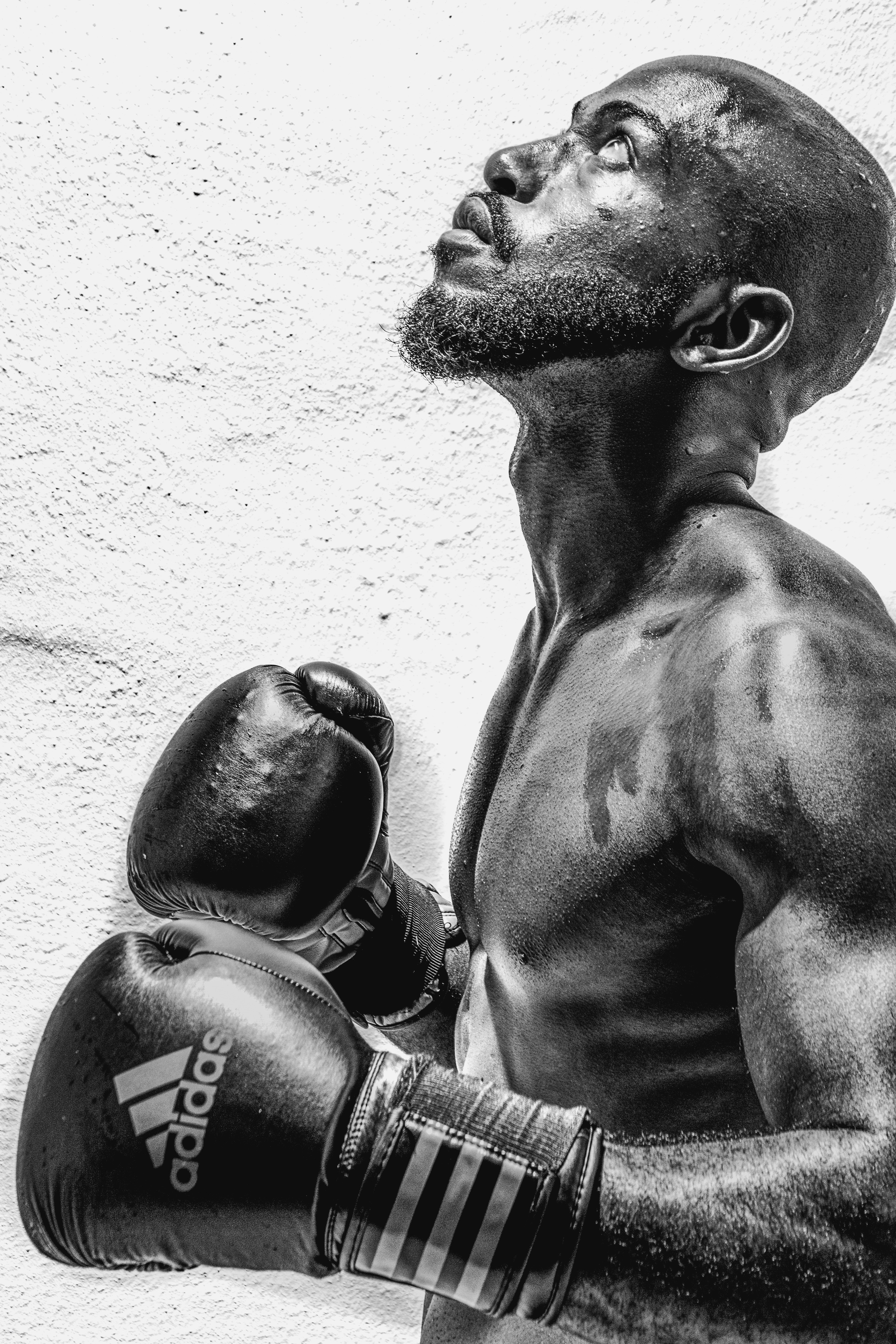 Black and white photo of a Black boxer whose athletic body is doused in sweat, gloved boxer mitts in almost a prayer position, looking up towards the sky as if summoning, thinking, or communicating with a higher belief right after a training or competition.