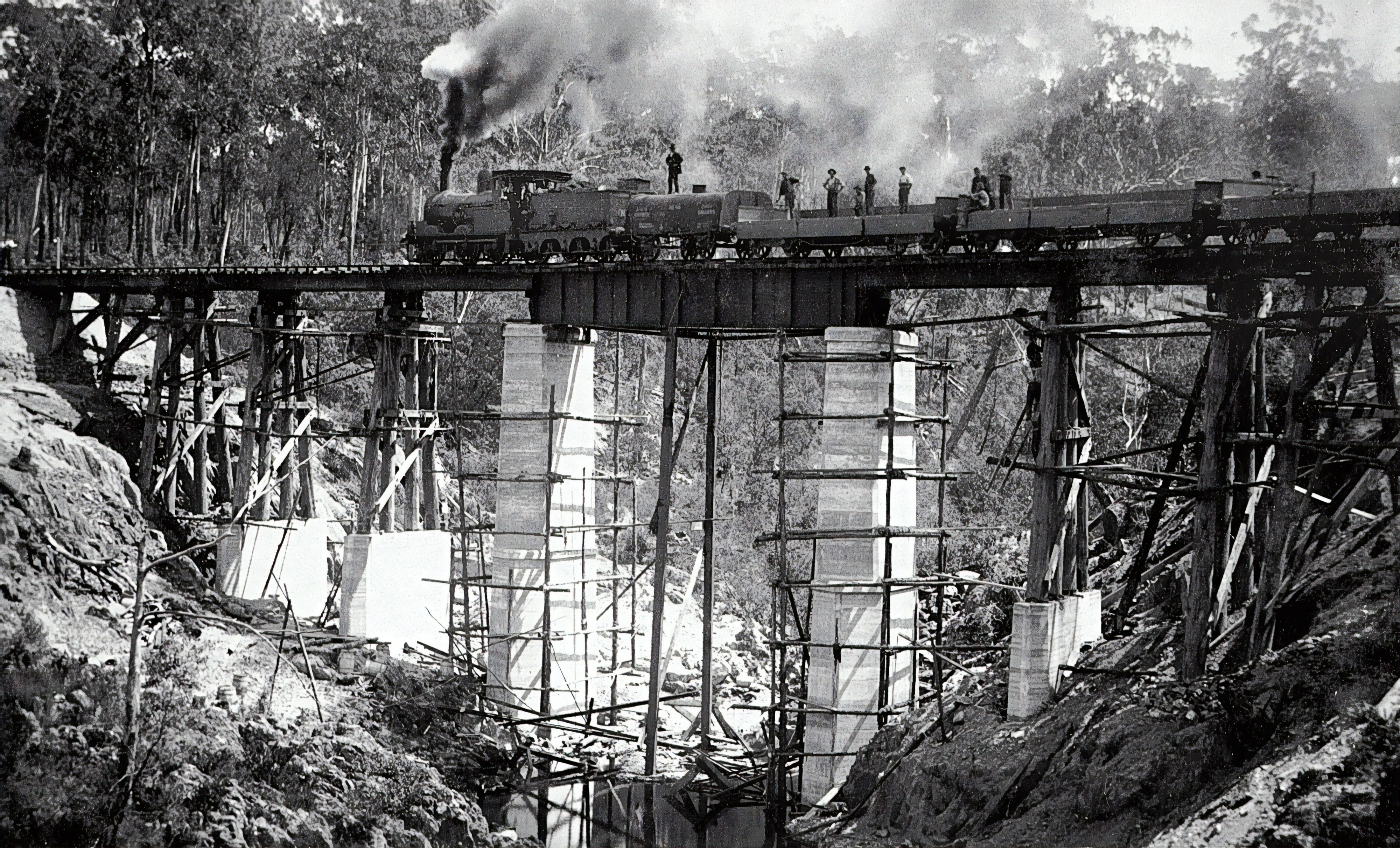 an old picture of a steam engine train on a rickety old bridge