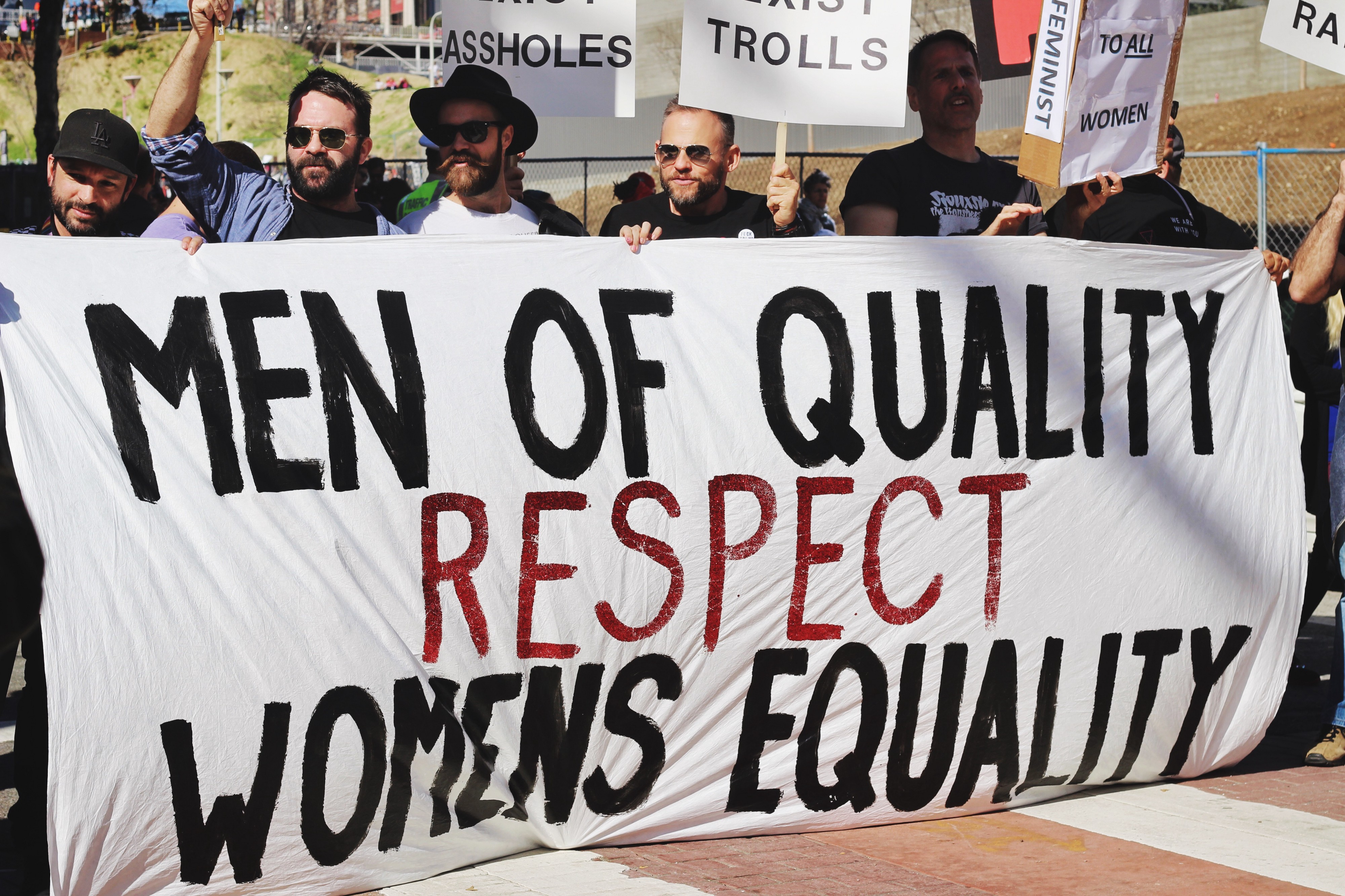 Men marching for women's rights. Four men holding a banner which reads Men of Quality Respect Women's Equality.