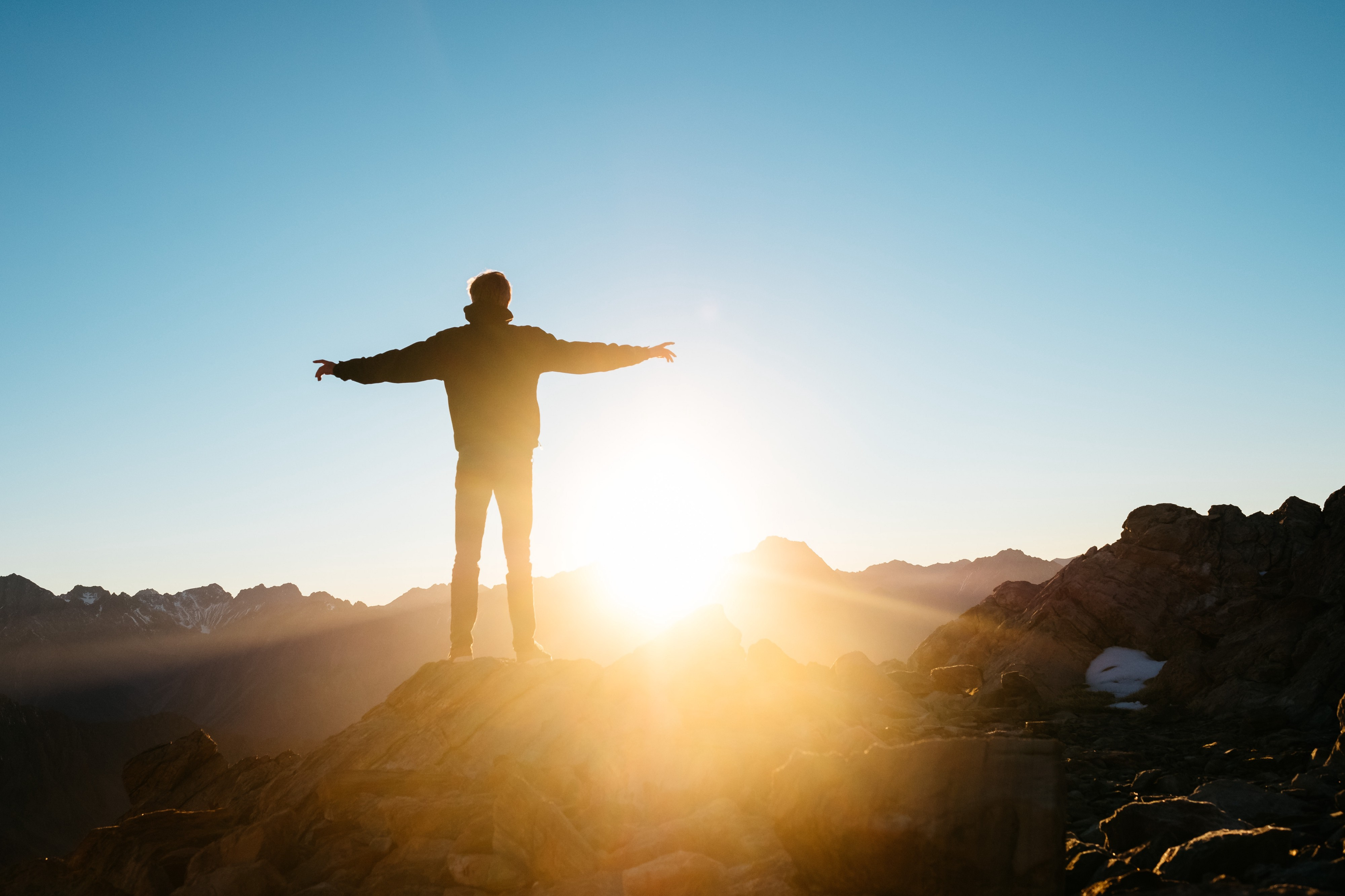 A man stands atop a mountain, as the sun rises before him. He has his arms outstretched as if he is free and liberated.