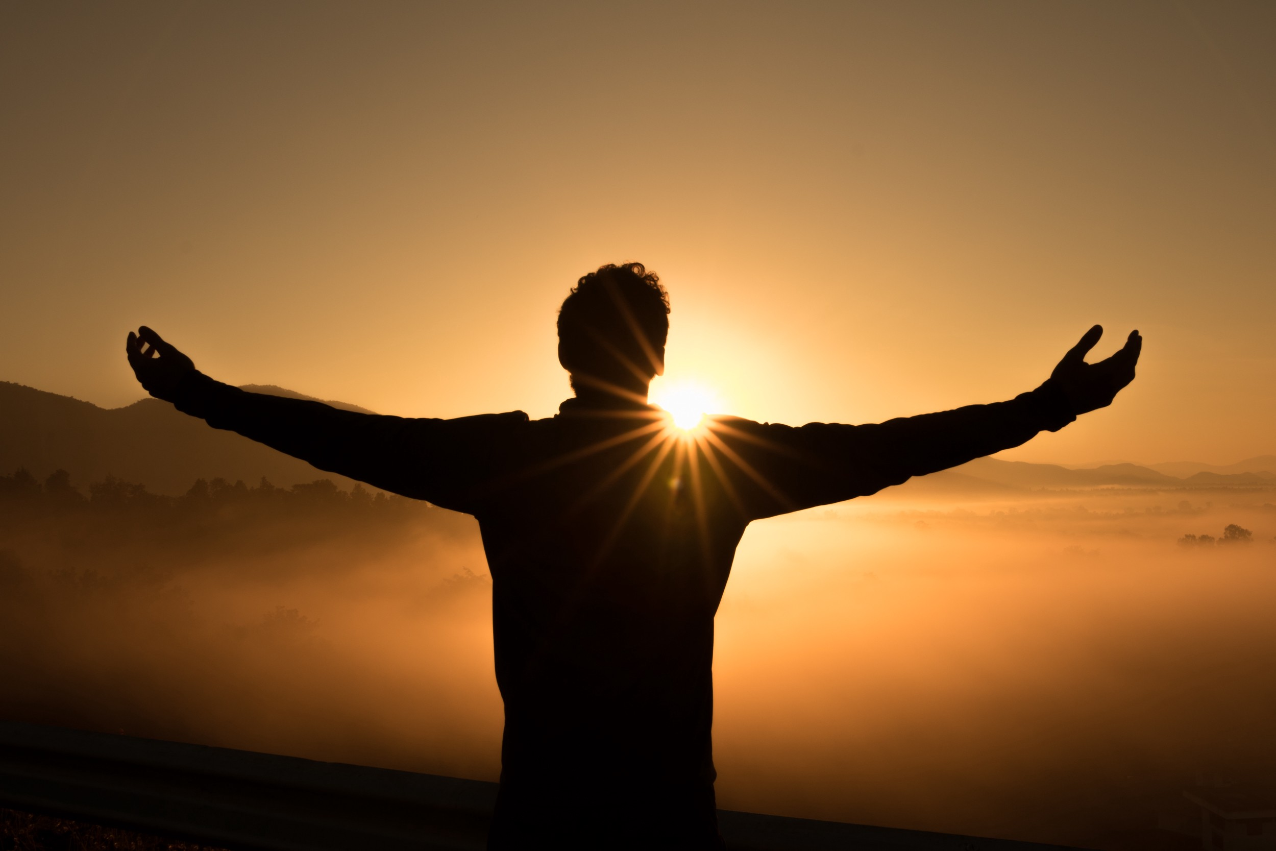 A silhouette of a man in the shape of a cross standing with arms reaching out while facing a golden sunrise