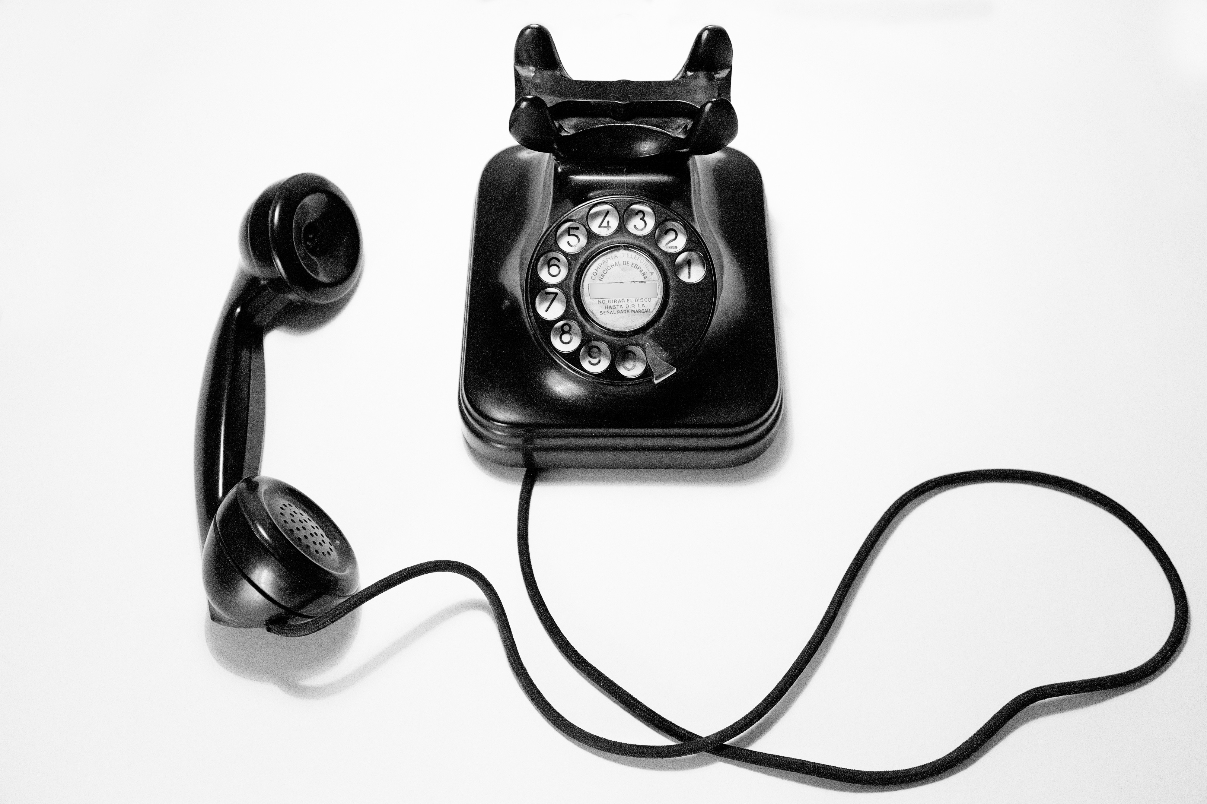 image of black rotary phone on a white background
