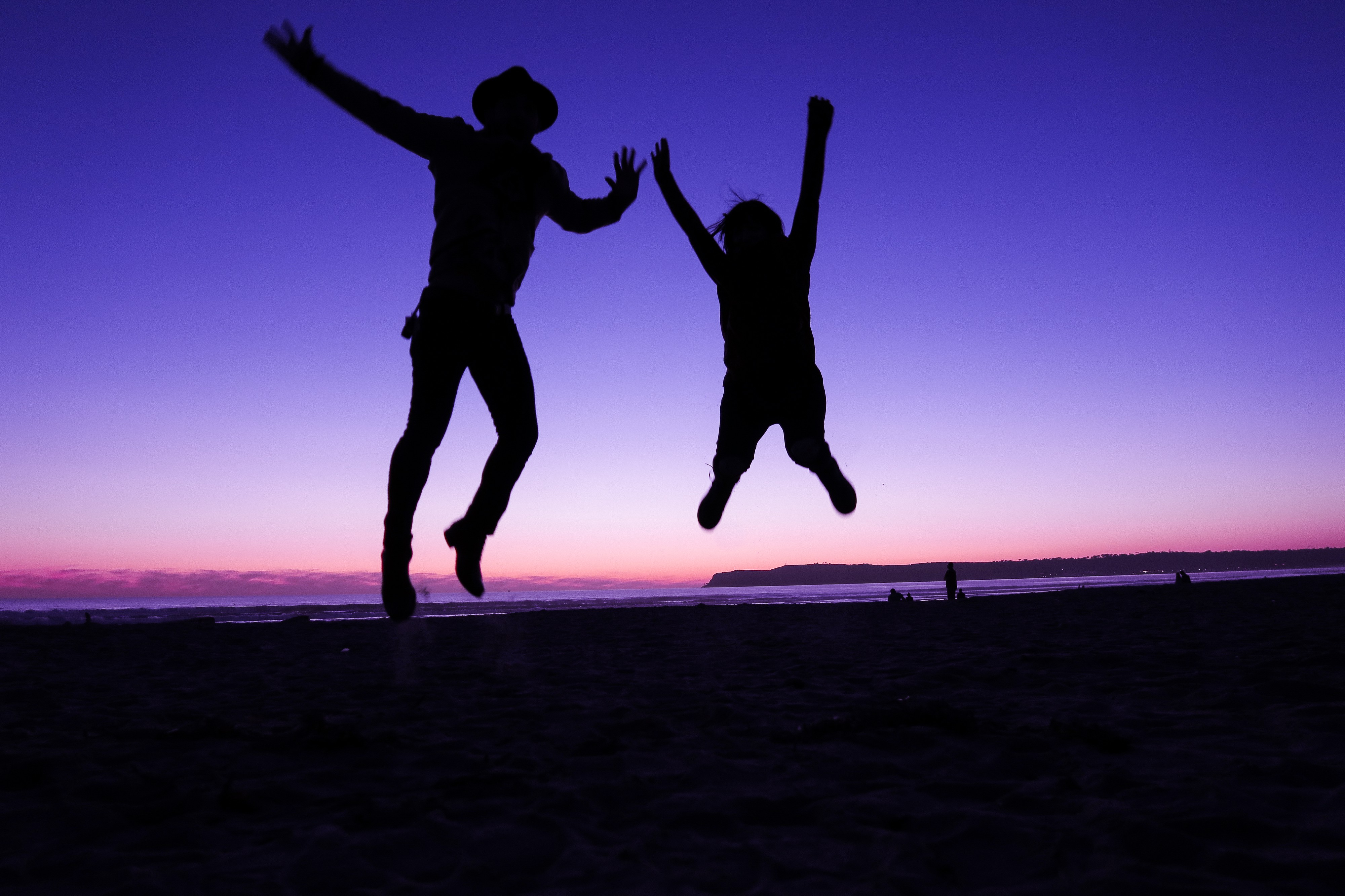 Two backlit humans — one in a cowboy hat — jump on a beach just after sunset.