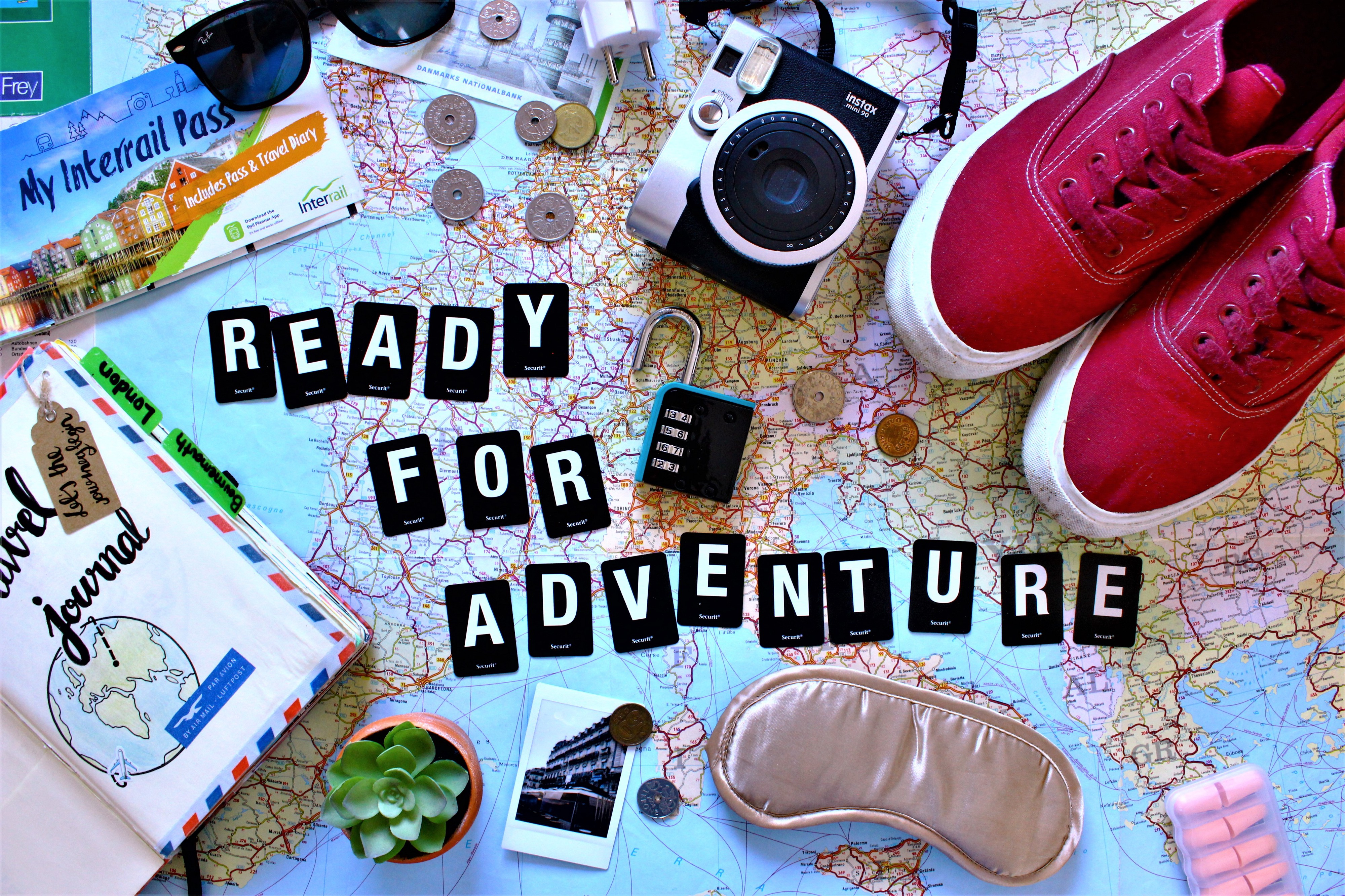 Ready For Adventure is spelt out in tiles across a world map. Shoes and a sleep mask, coins and rail pass are also spread out