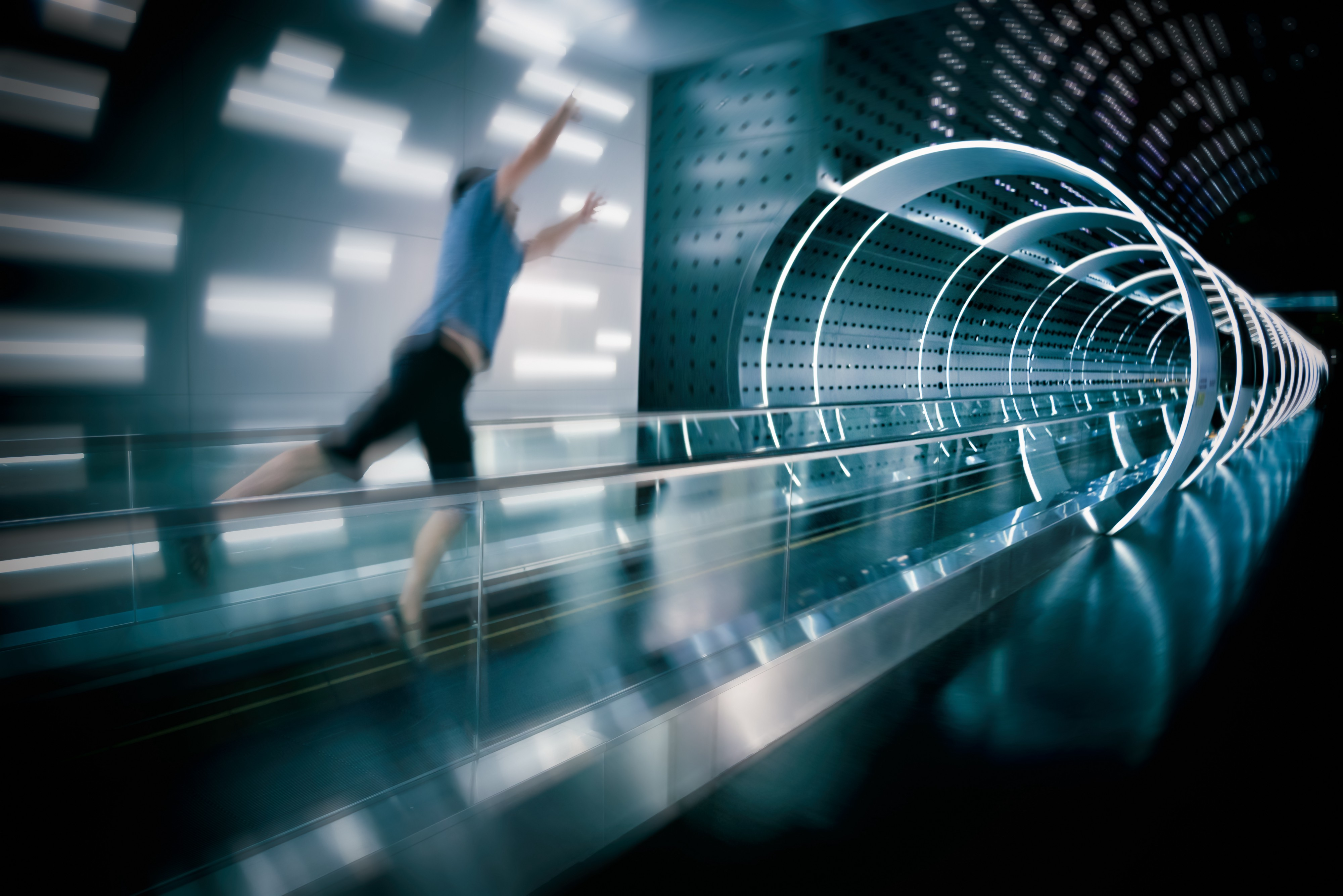 A man jumping forward towards a space age looking tunnel