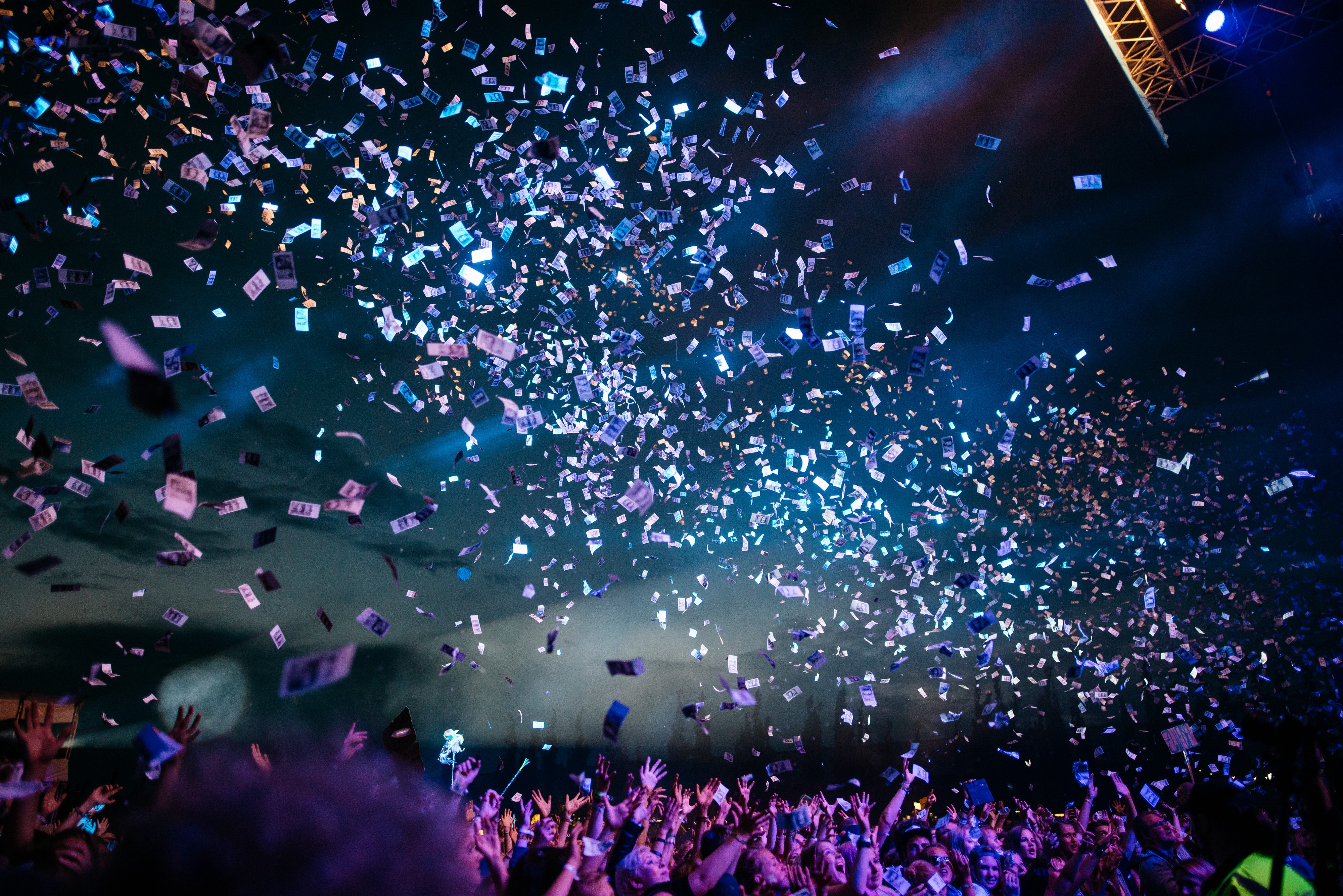 Confetti falling at a concert with bright colored lights