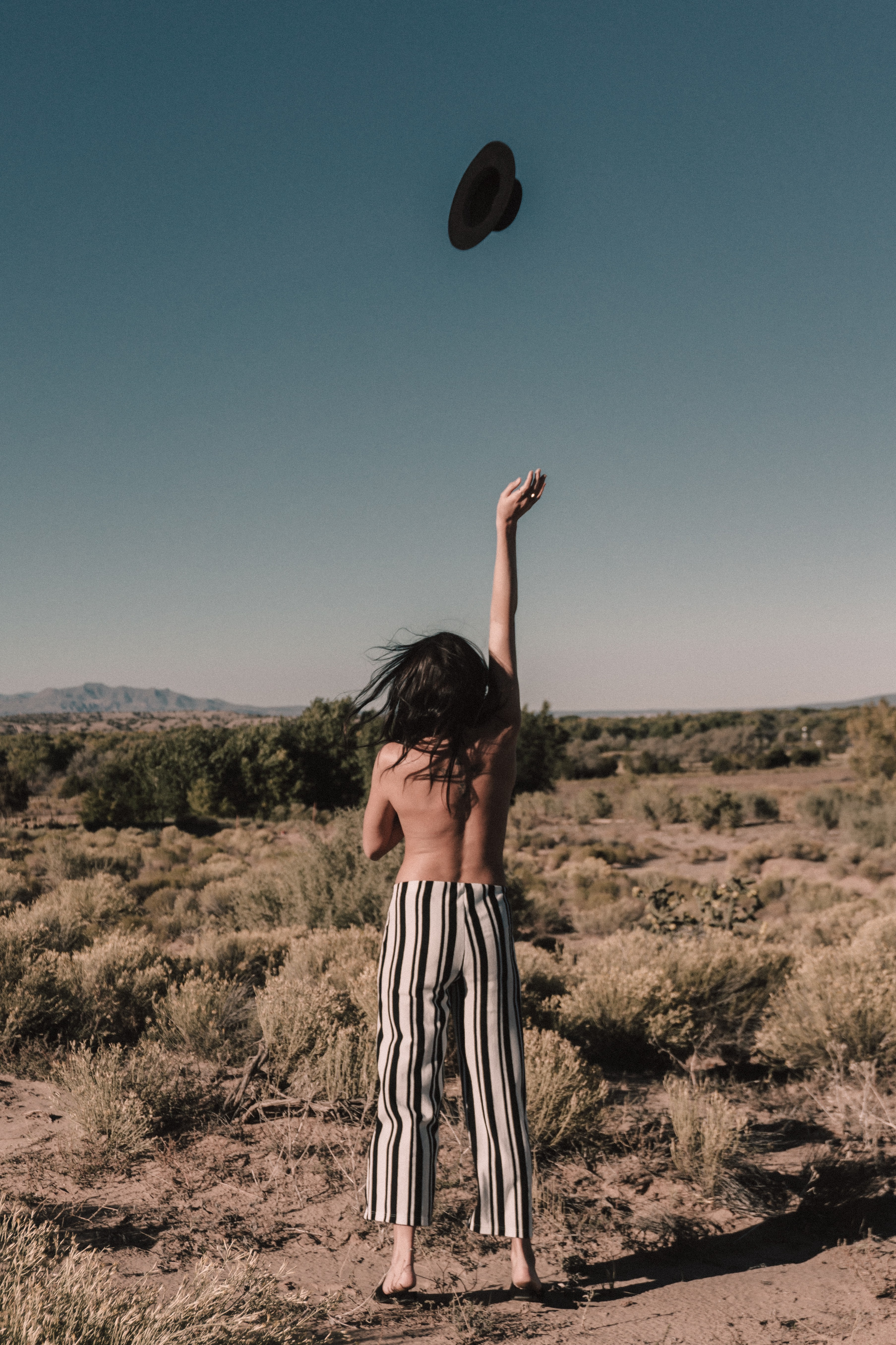 Topless brunette woman facing away from the camera, throwing her hat in the air with her hand raised
