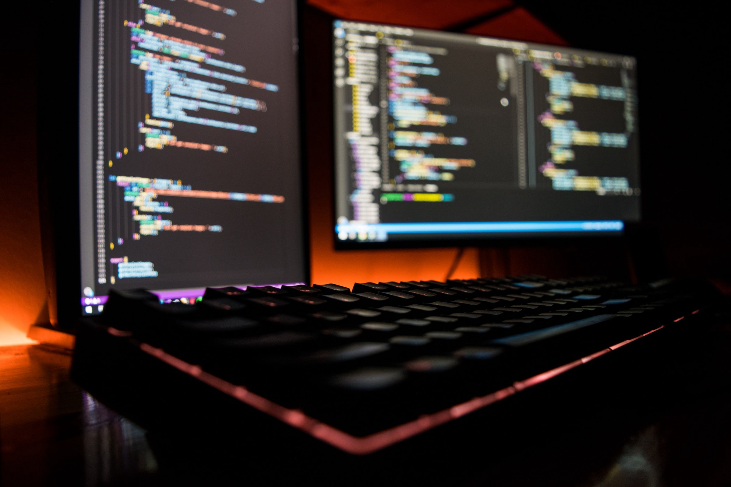 Two monitors displaying computer code, with a keyboard in front. The monitors are back-lit by an orange glow.