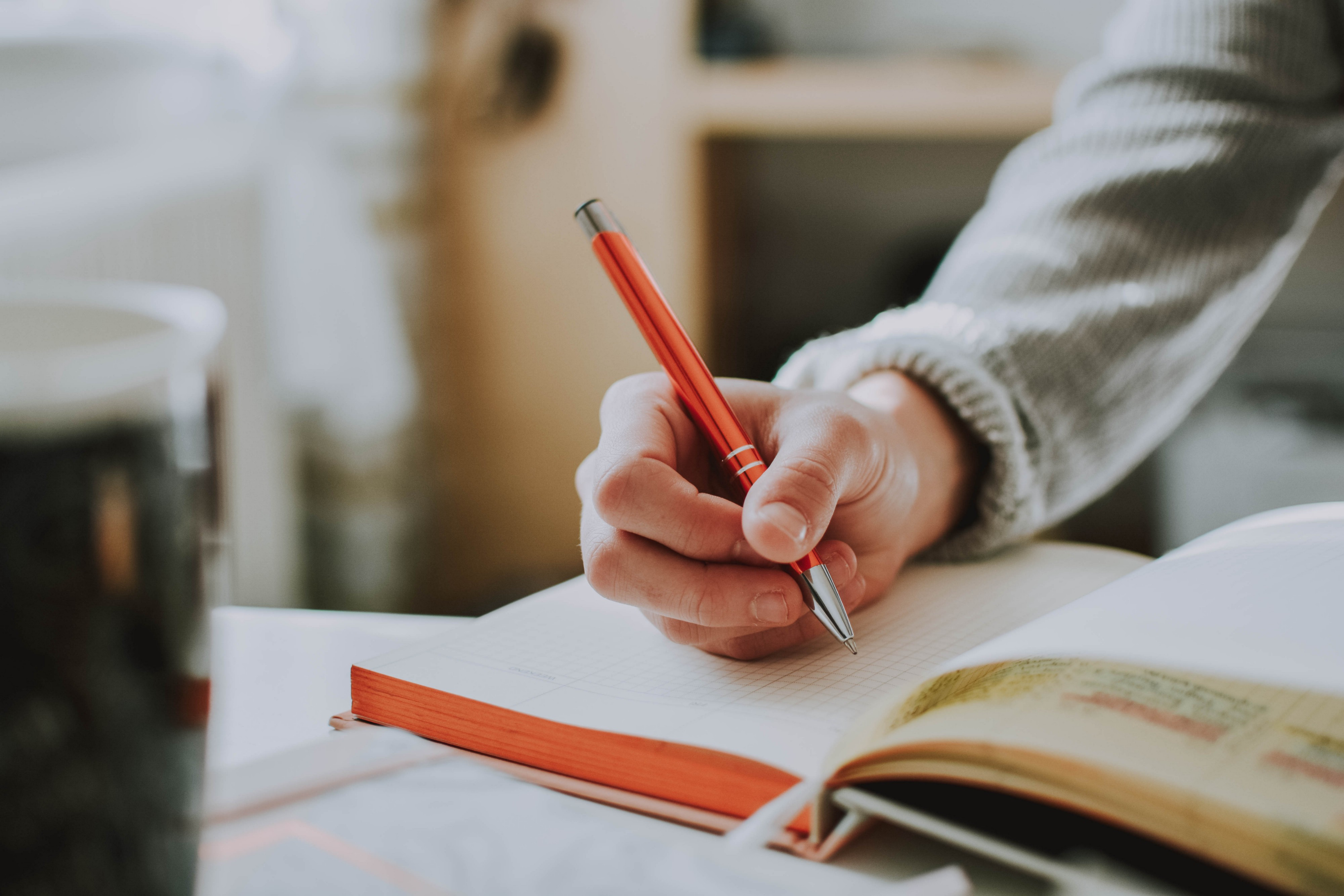 A person sits at a table writing with an orange coloured pen in a thick notebook.