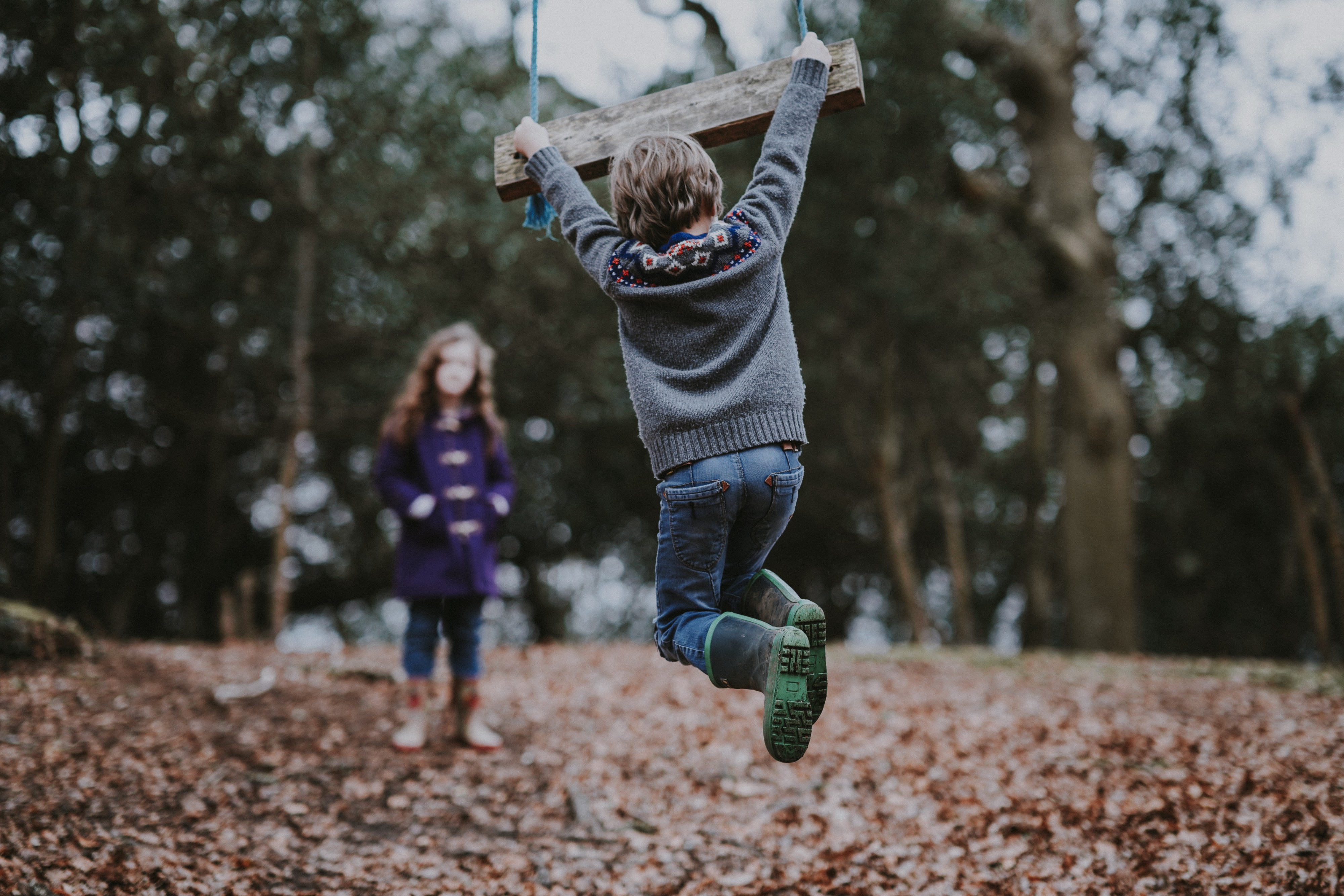 A brother swings on a wooden swing, above a path full of crisp autumn leaves. In the distance is his sister, hands in pocket, watching.