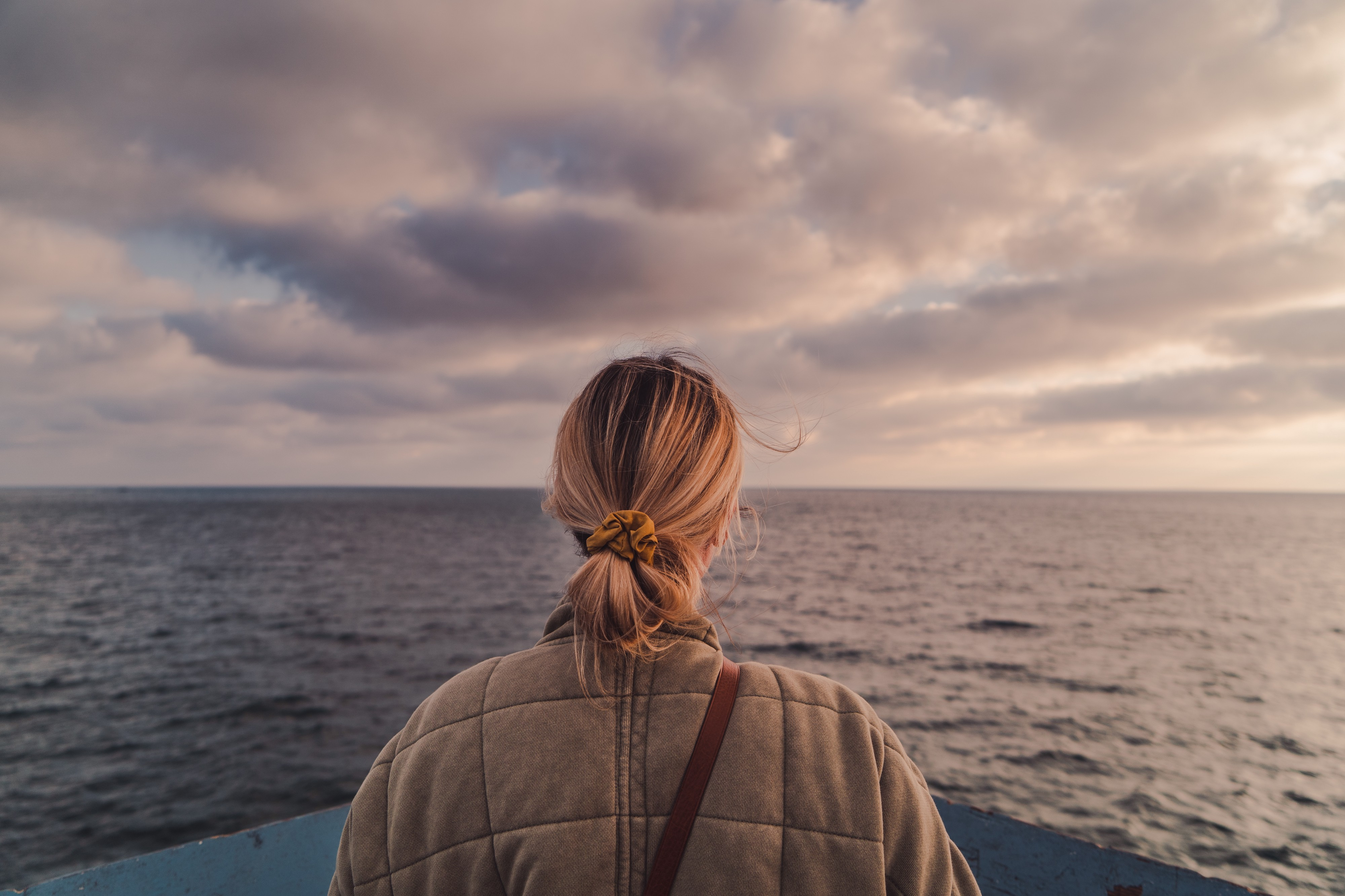 A woman stands at the front of a boat, looking out to the sea in front of her. The sky is cloudy and grey as the sun sets.
