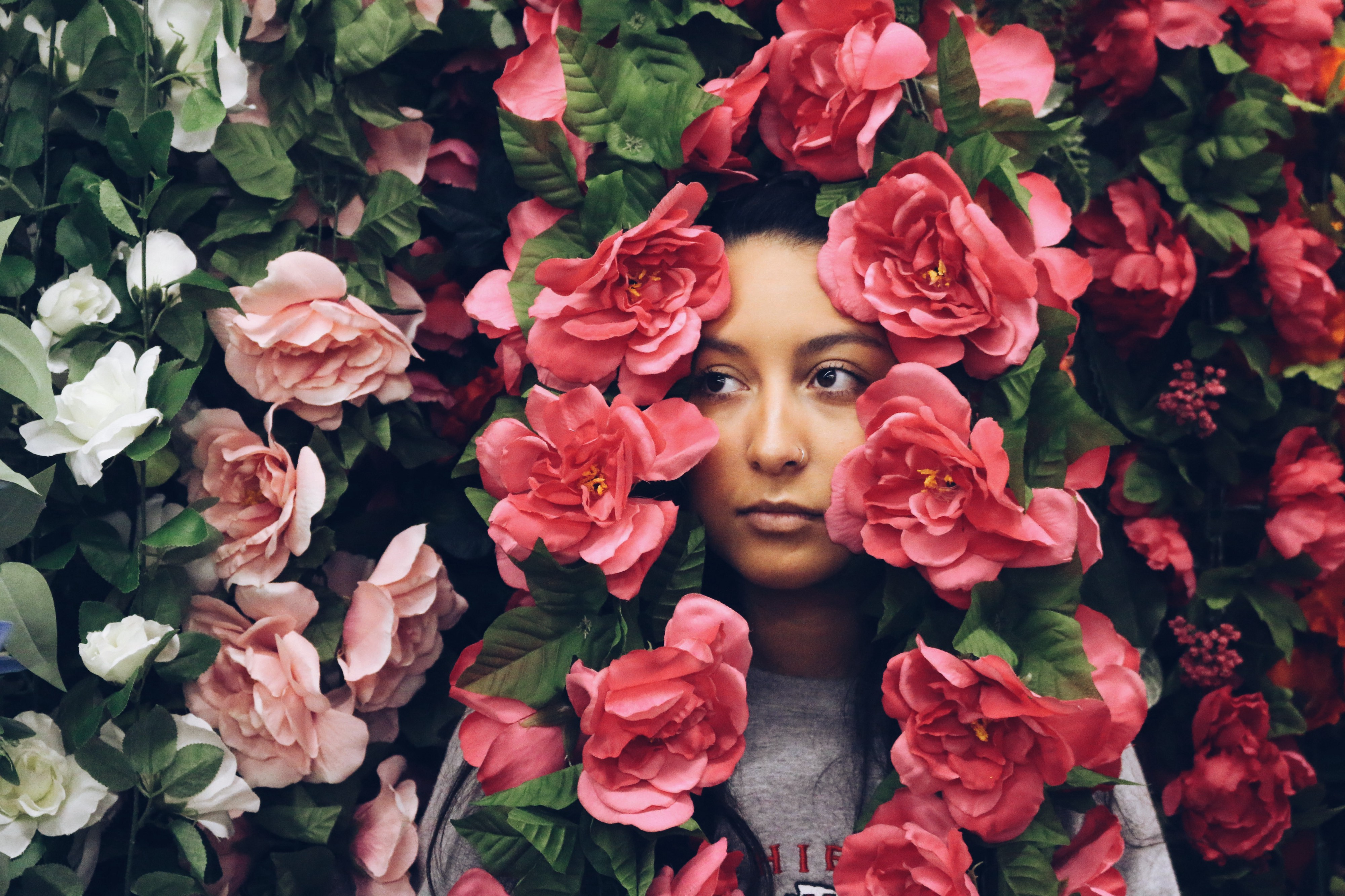 A woman stands amongst a wall of flowers, with the flowers cascading around her face. She looks thoughtful.