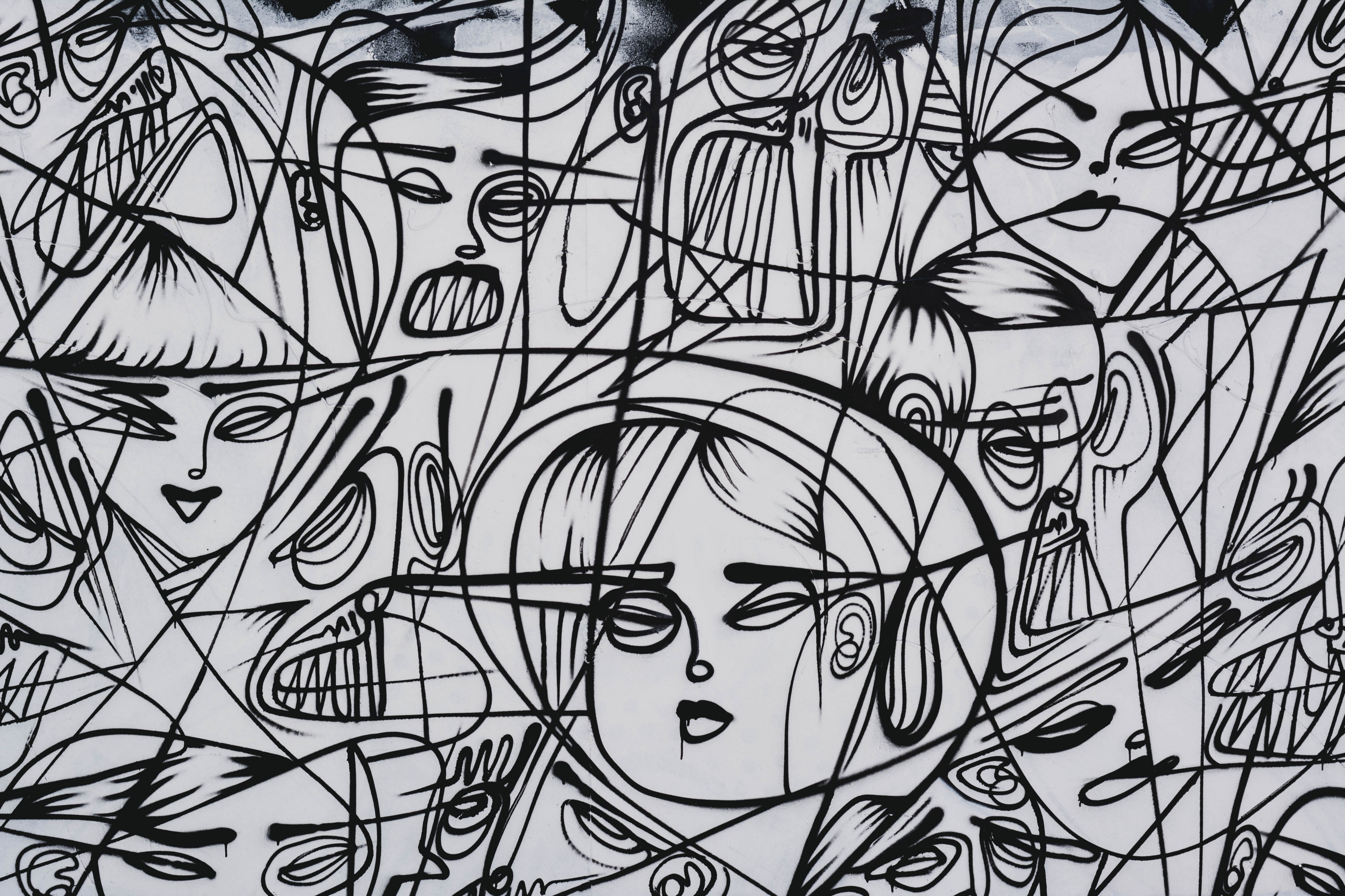 black and white drawing of human faces, connected and partially crossed out by black lines on a white background