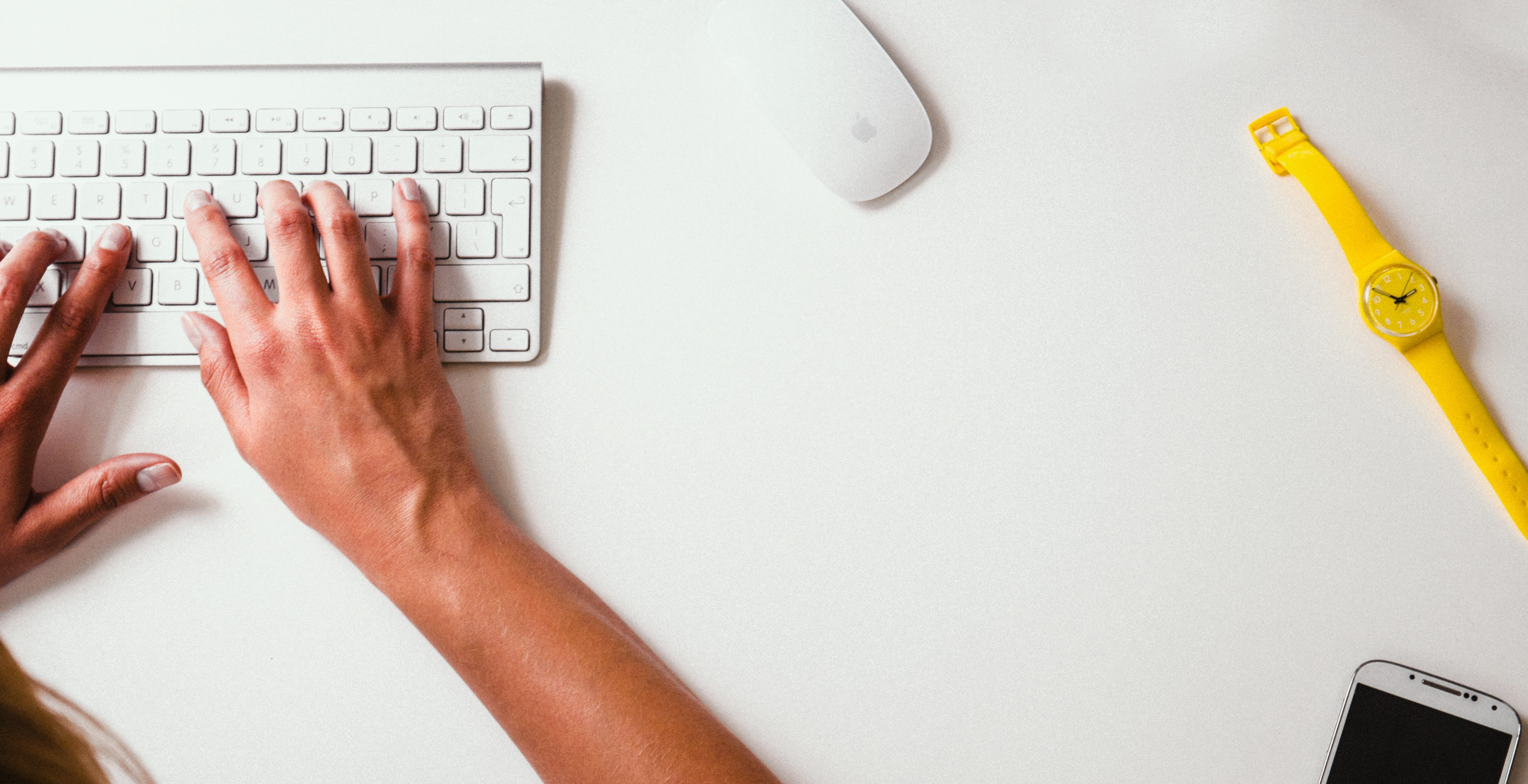 A top-down photo of a person's hands on top of a white keyboard