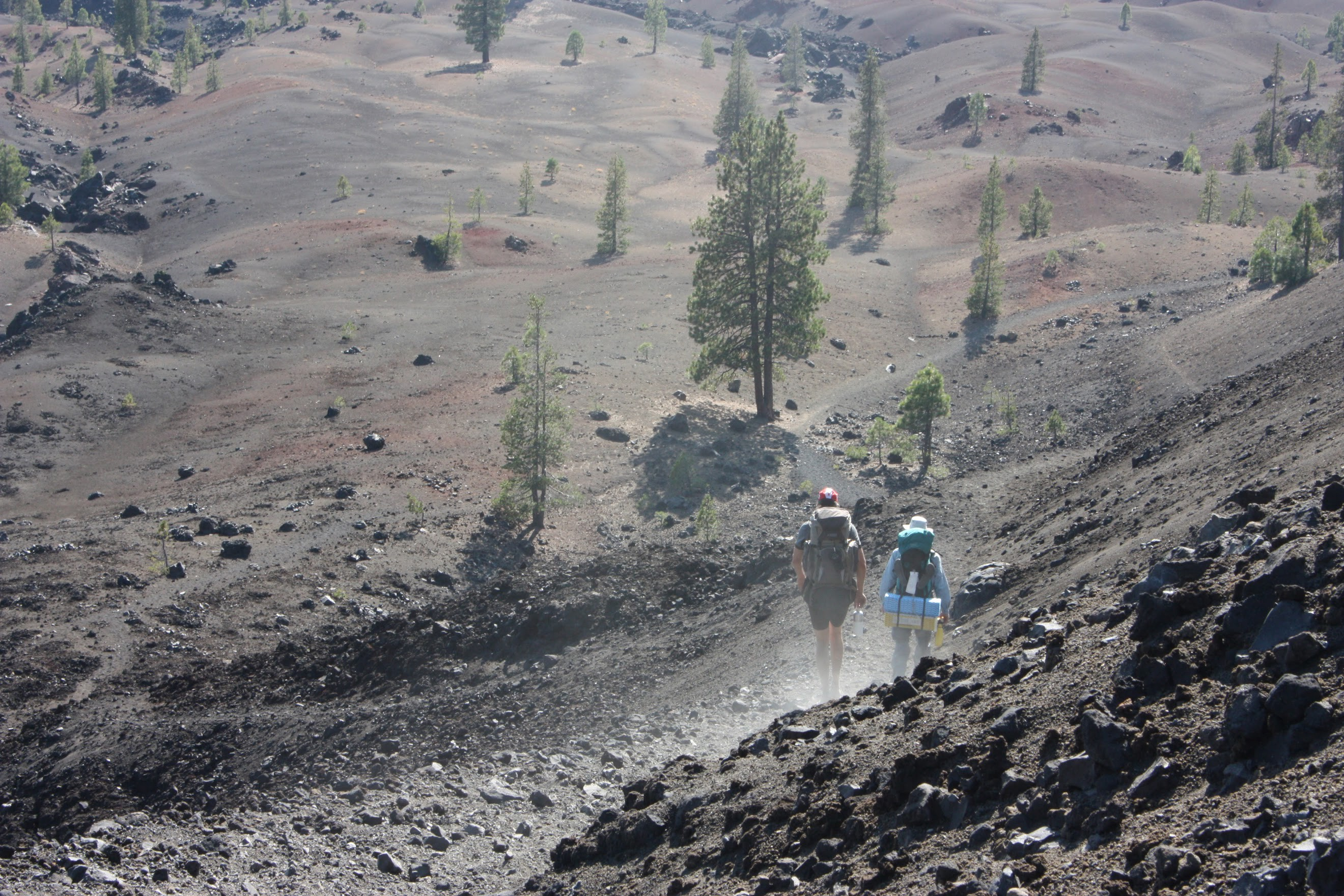 Hikers descending down a dusty volcanic trail