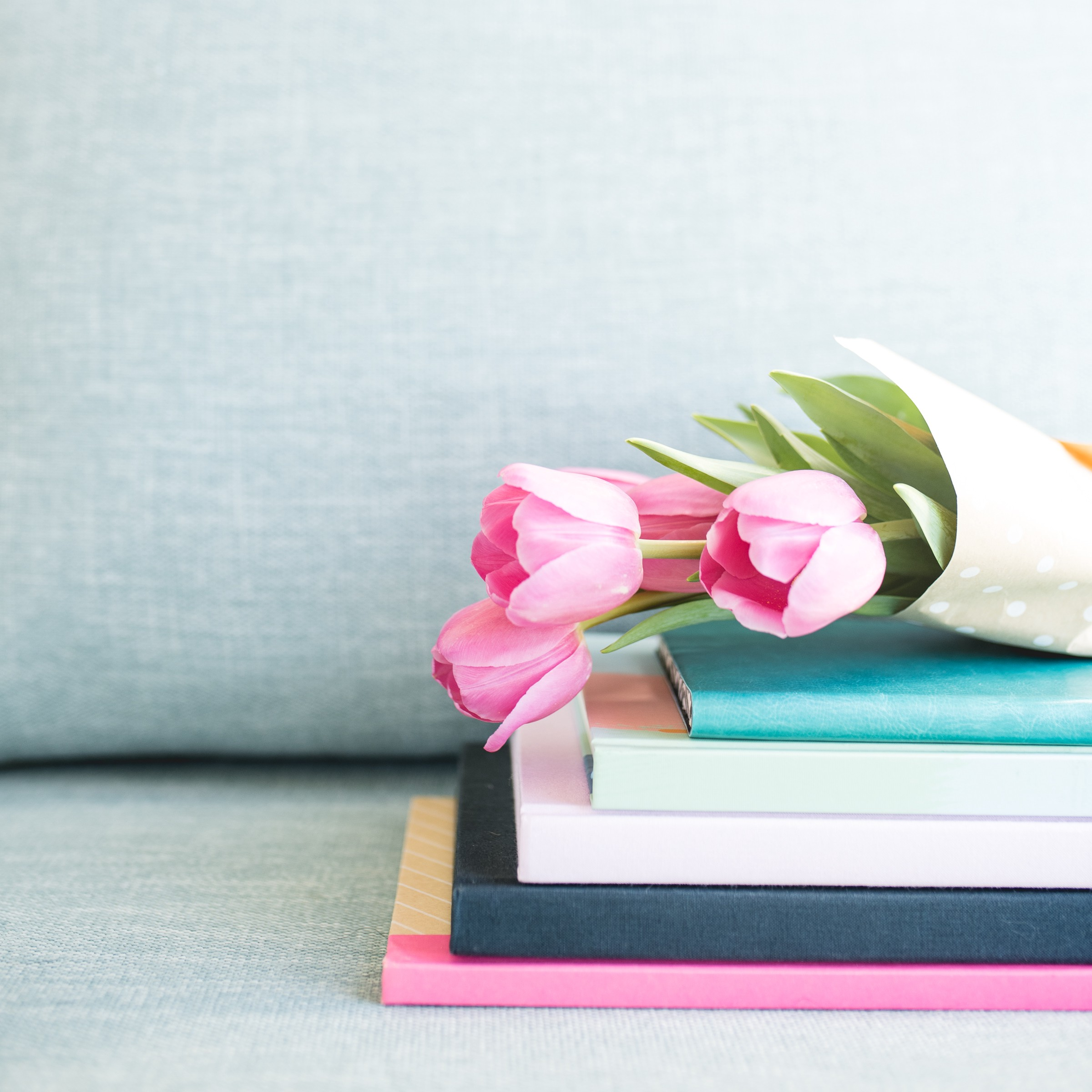 Light pink tulips wrapped in white paper and placed over a short stack of pastel colored bound-edged notebooks
