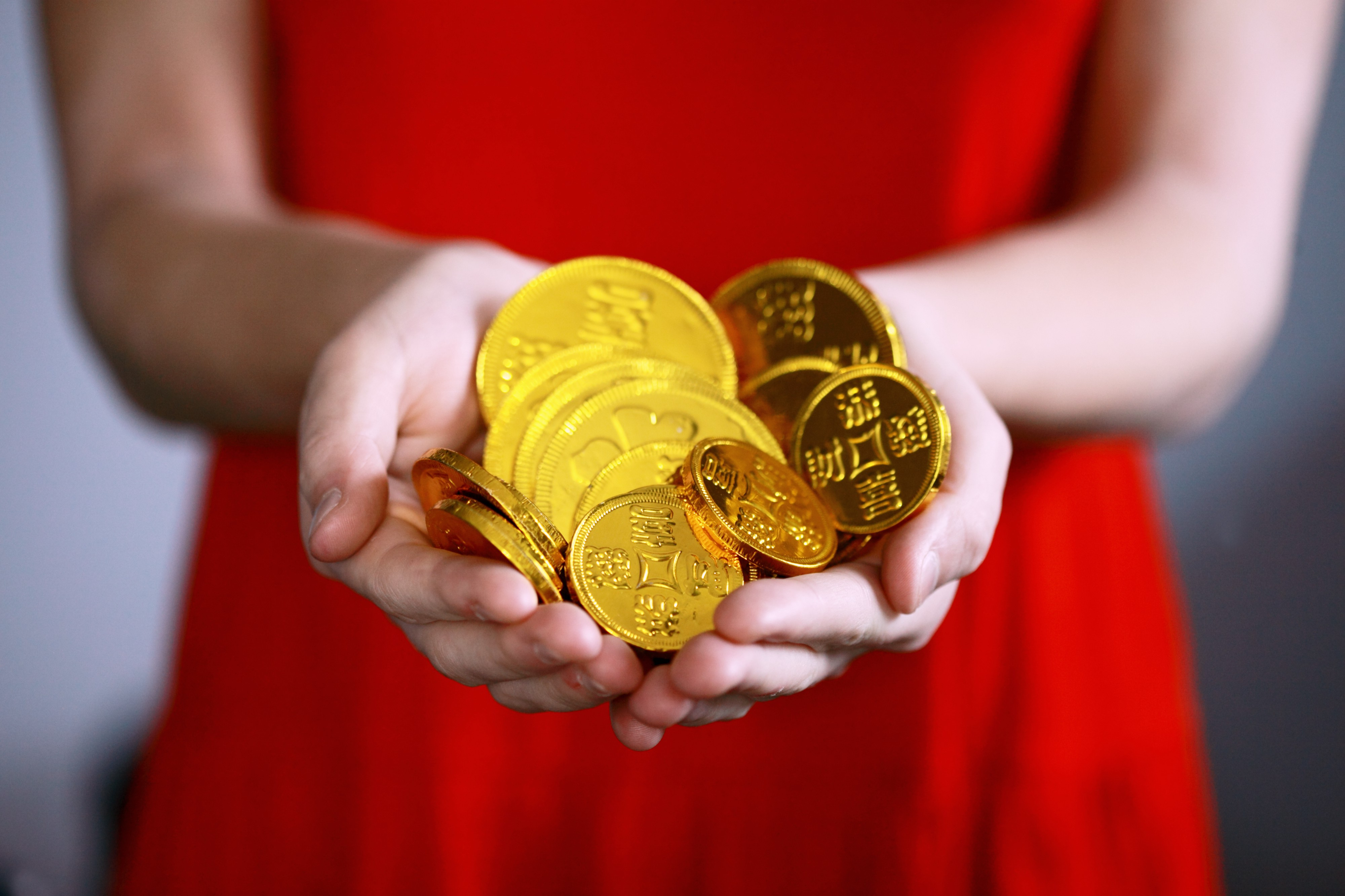 Girl in red dress holding a pile of gold cryptos with both hands cupped in front of her