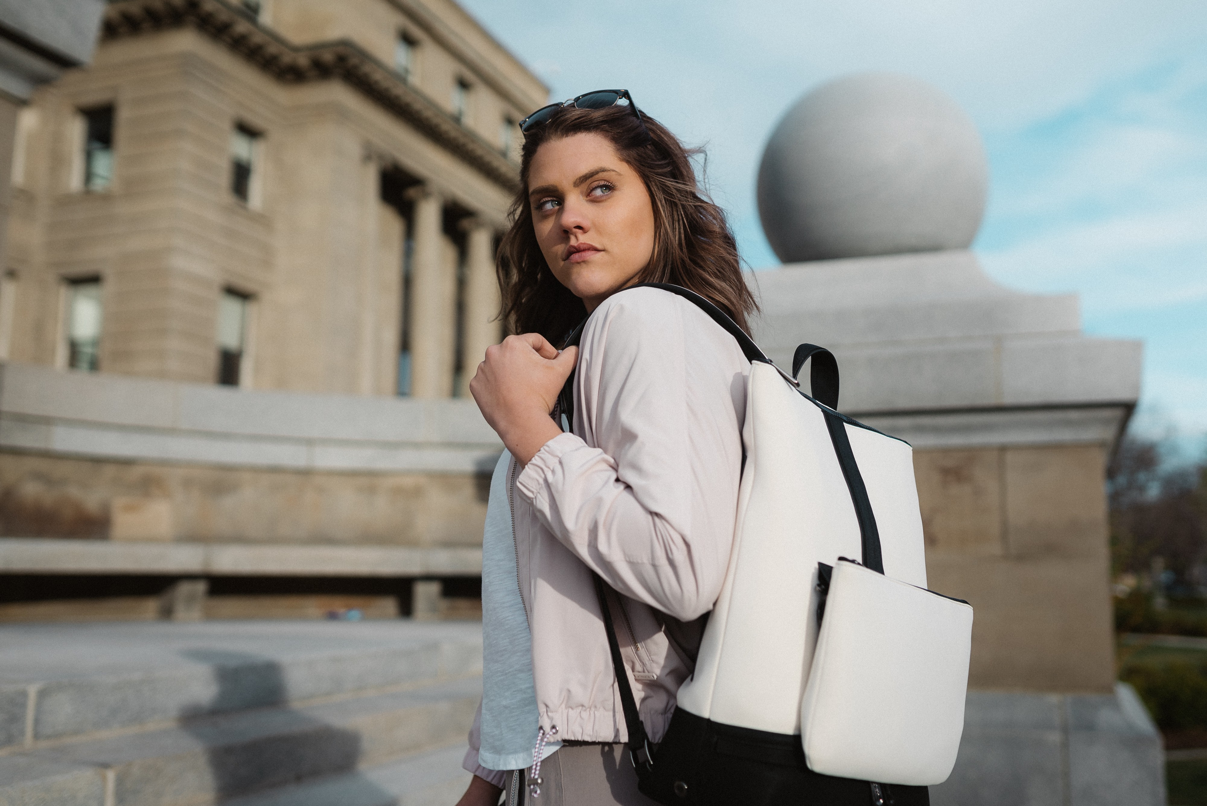 A woman with brown hair stands on some steps, looking over her shoulder. She has a white backpack style handbag slung over her shoulder.