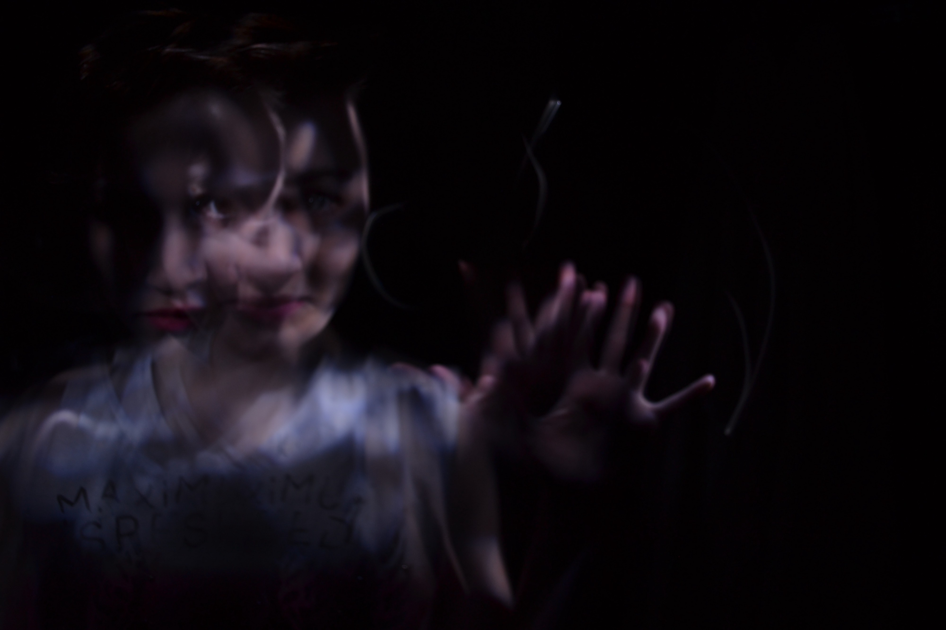 A darker image of a woman, where the woman is not in focus, and stretching out her hands, to go with the story about a man in a motel, and something under the bed kept him awake.