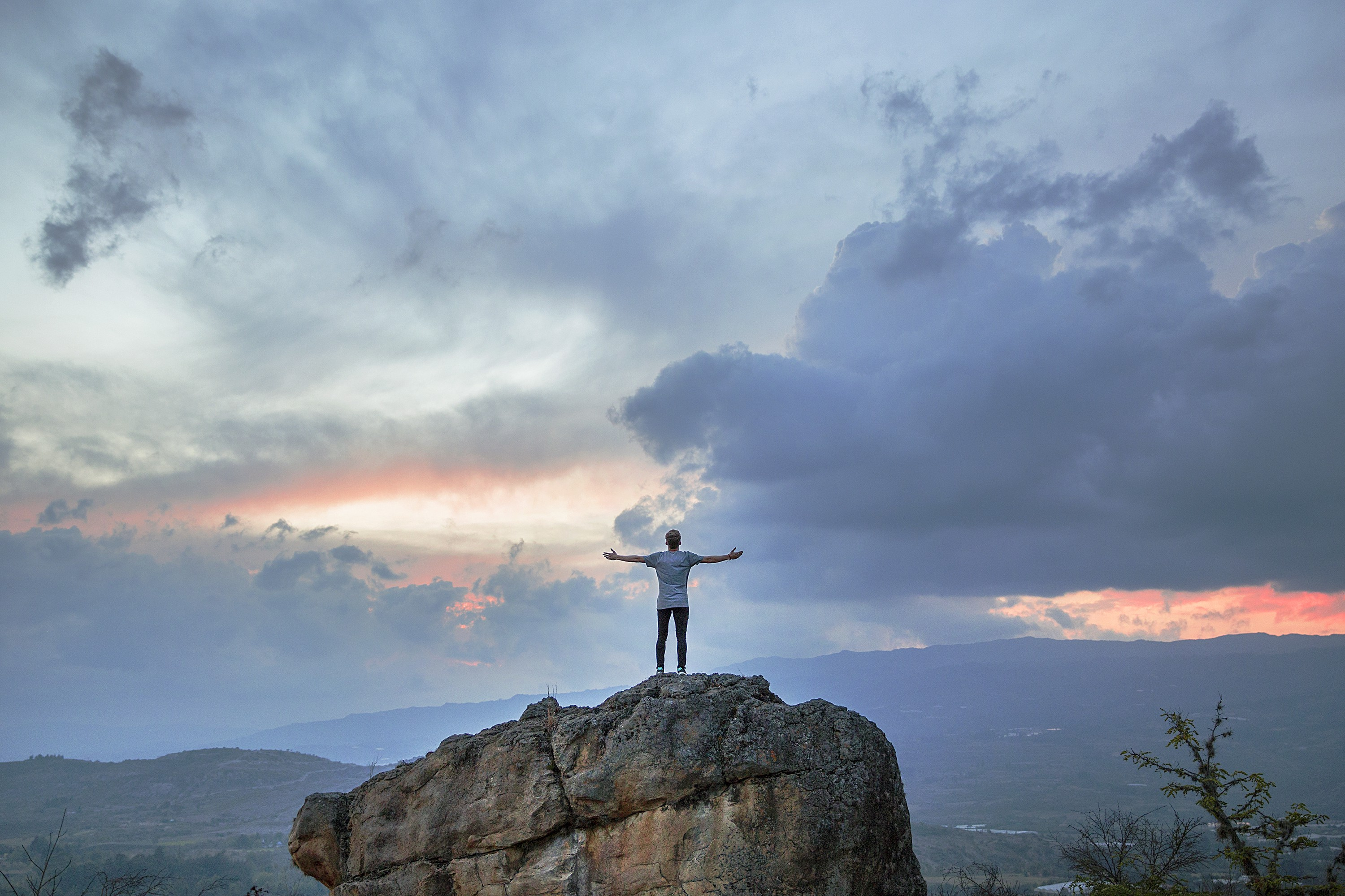 A man stands on top of a rock with outspread arms, gazing out into a cloudy sunset