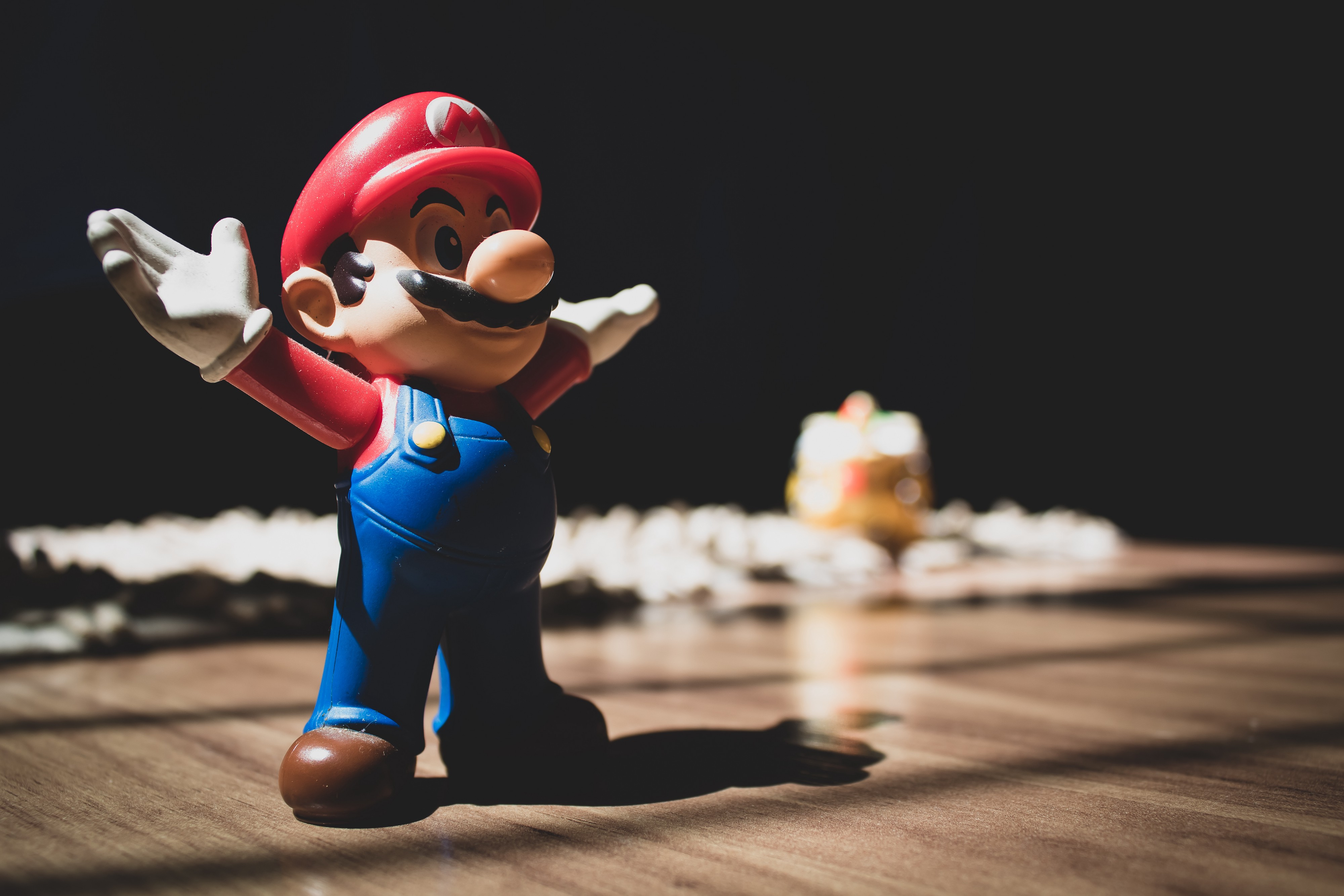Small figurine of Mario with arms extended out, sitting on a table