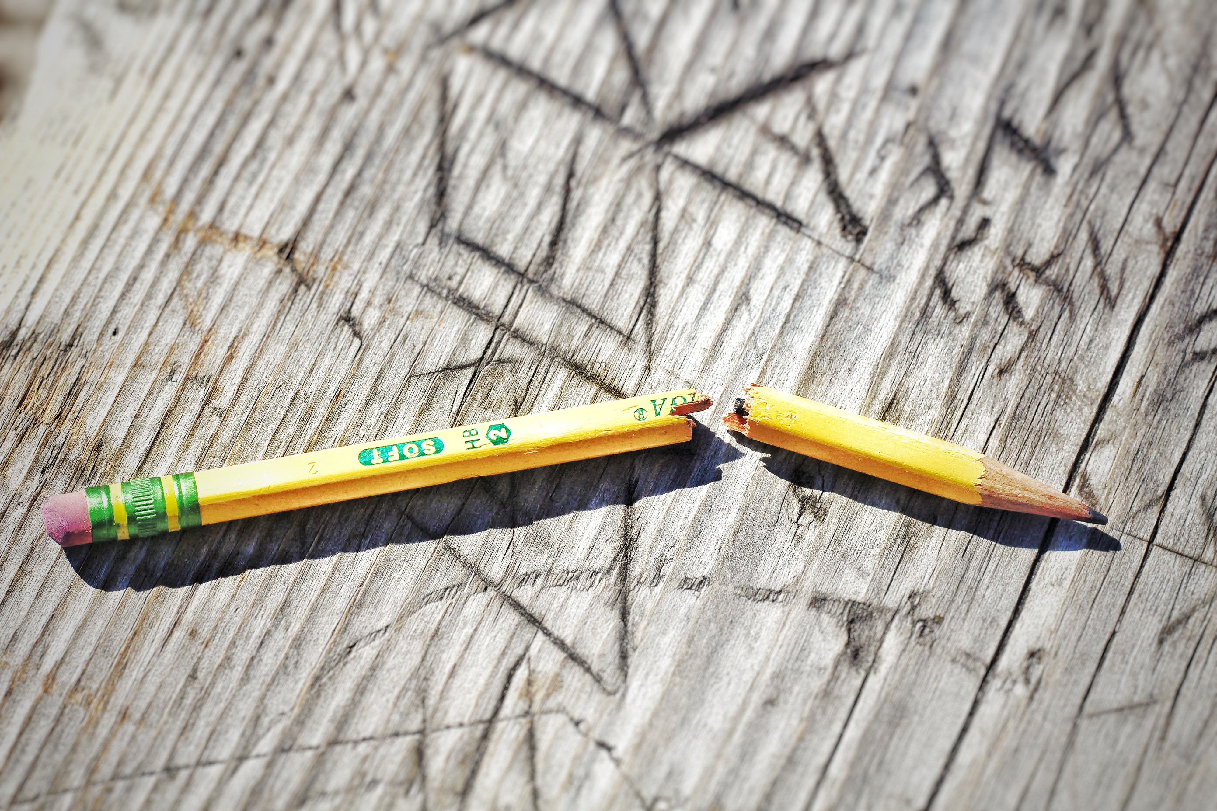 Close-up of a snapped pencil atop a worn picnic table vandalized by initials and the like.