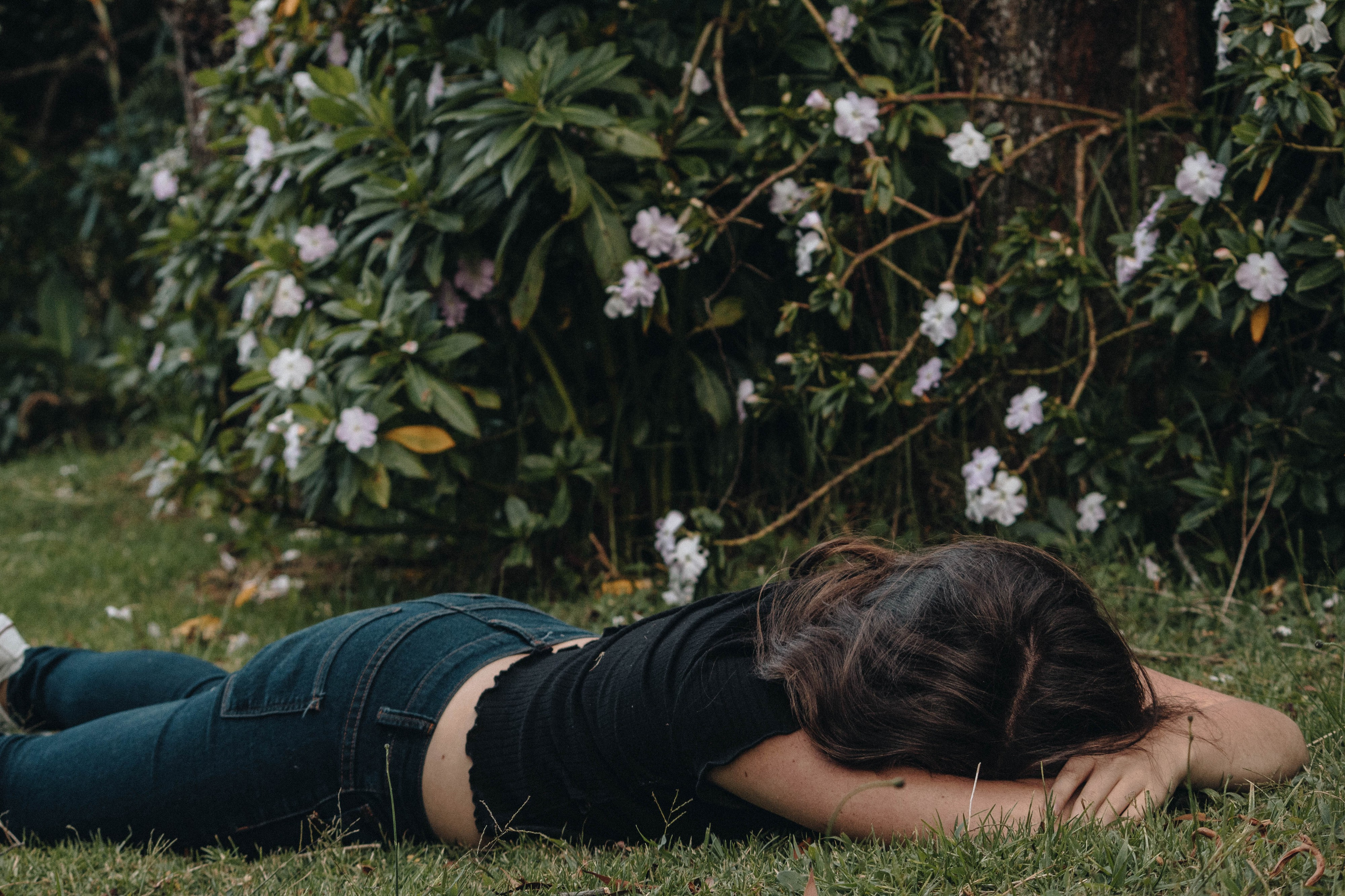 A woman wearing jeans and a black top lies face down in grass. A bush with flowers are behind her.