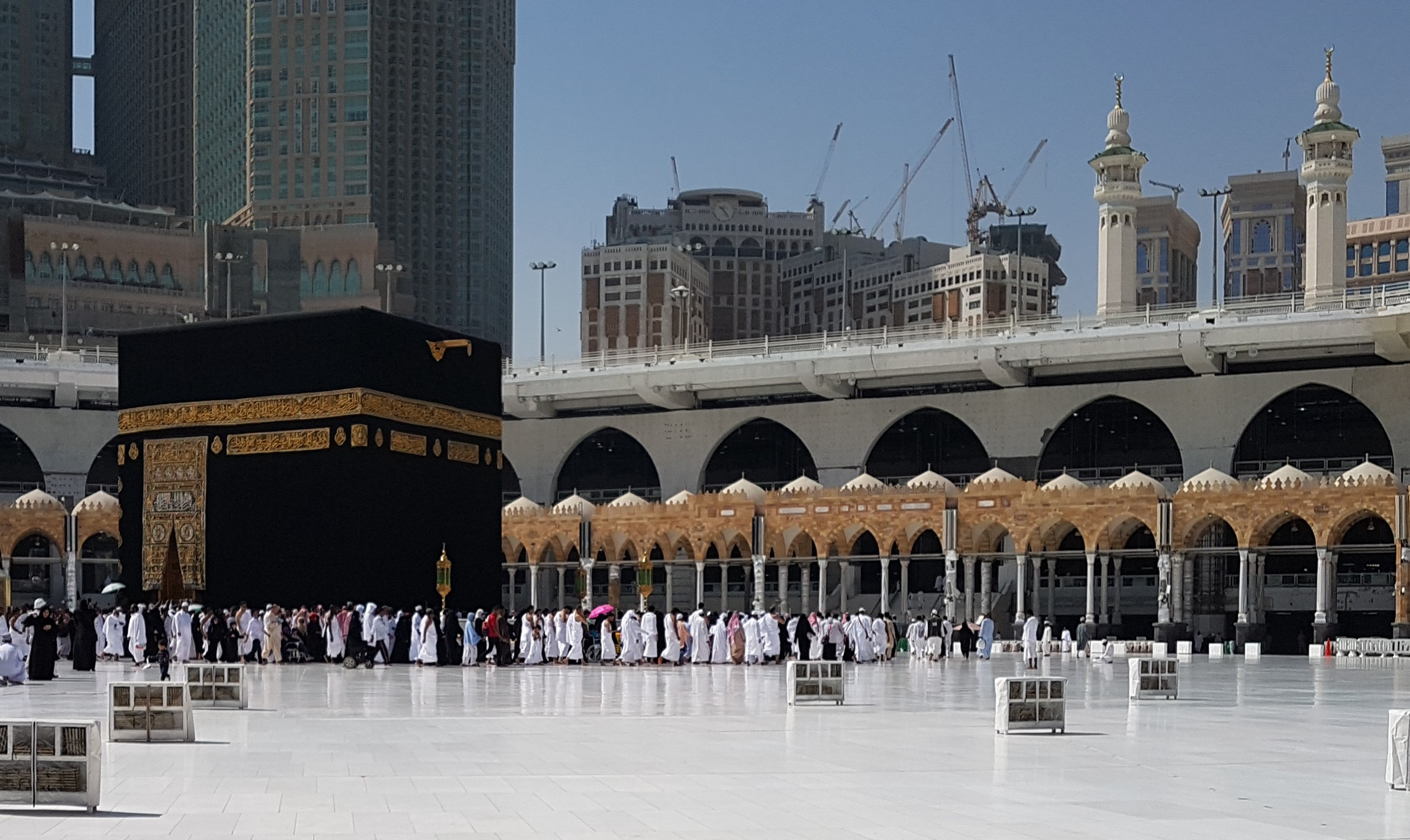 Picture of Kaba (The House of God as per Islam) in its Black embroidered Kiswah and the white marble floor with pilgrims making the rounds in the foreground.