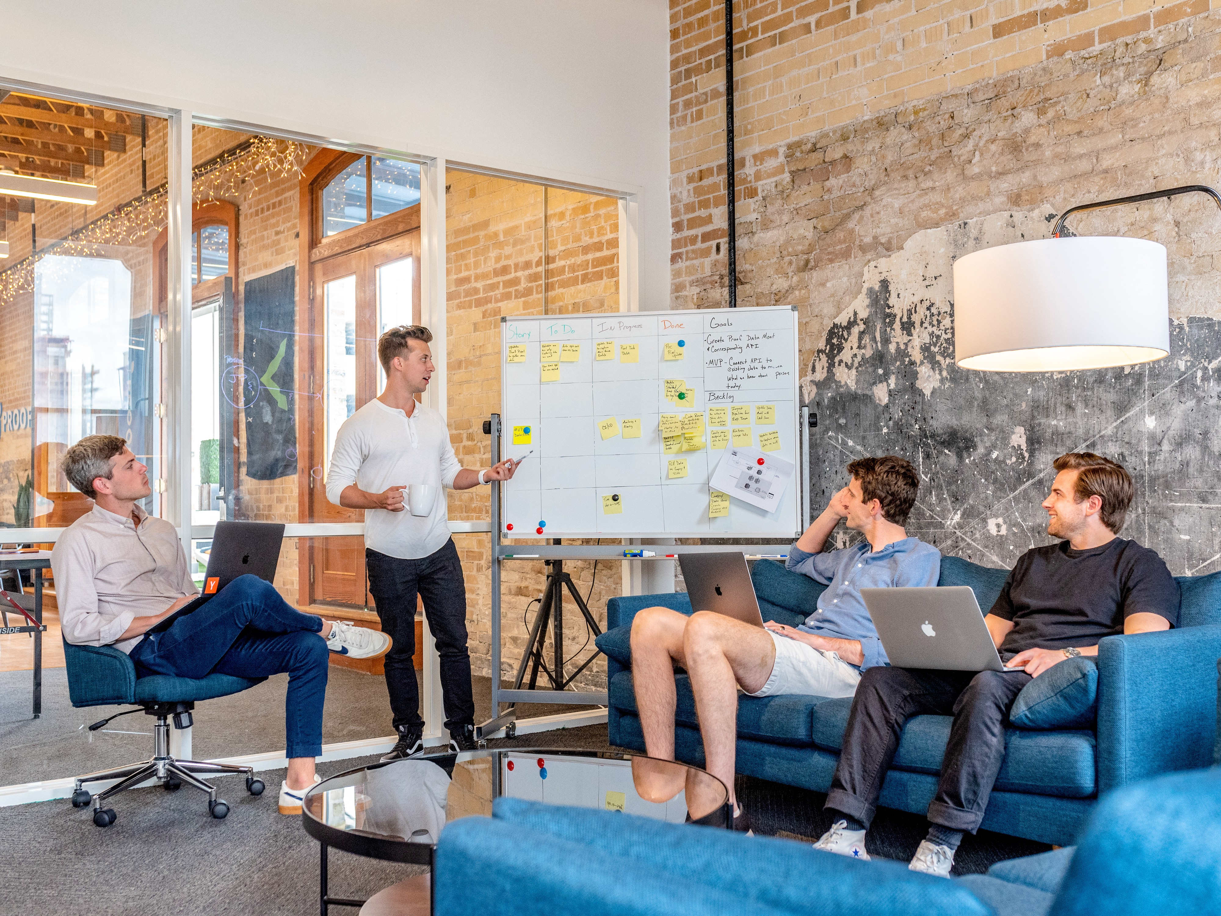 A startup image, where some people are sitting and discussing on a topic through whiteboard