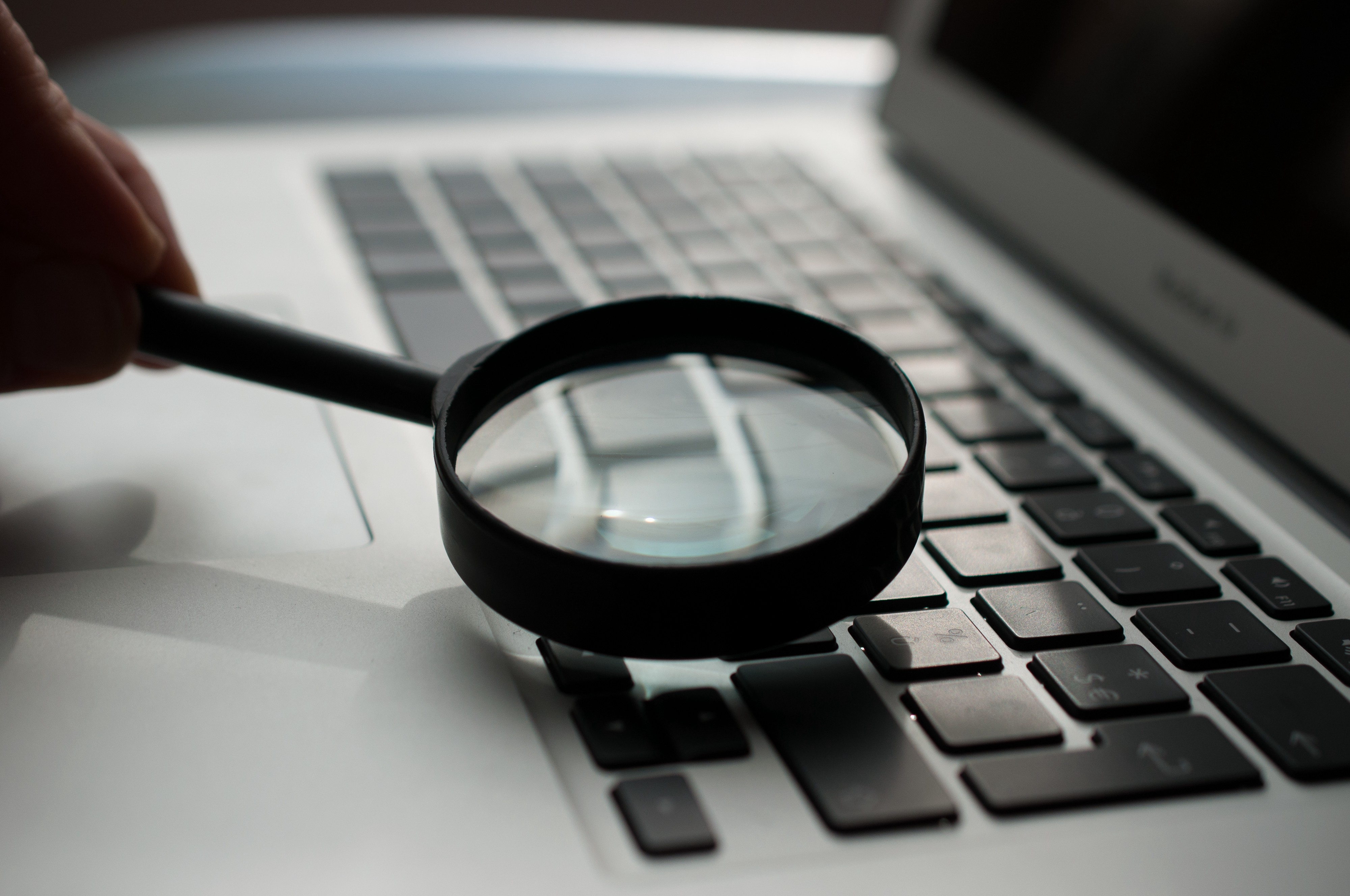 Somebody pointing a magnifying glass on a Macbook Air keyboard, while it's off