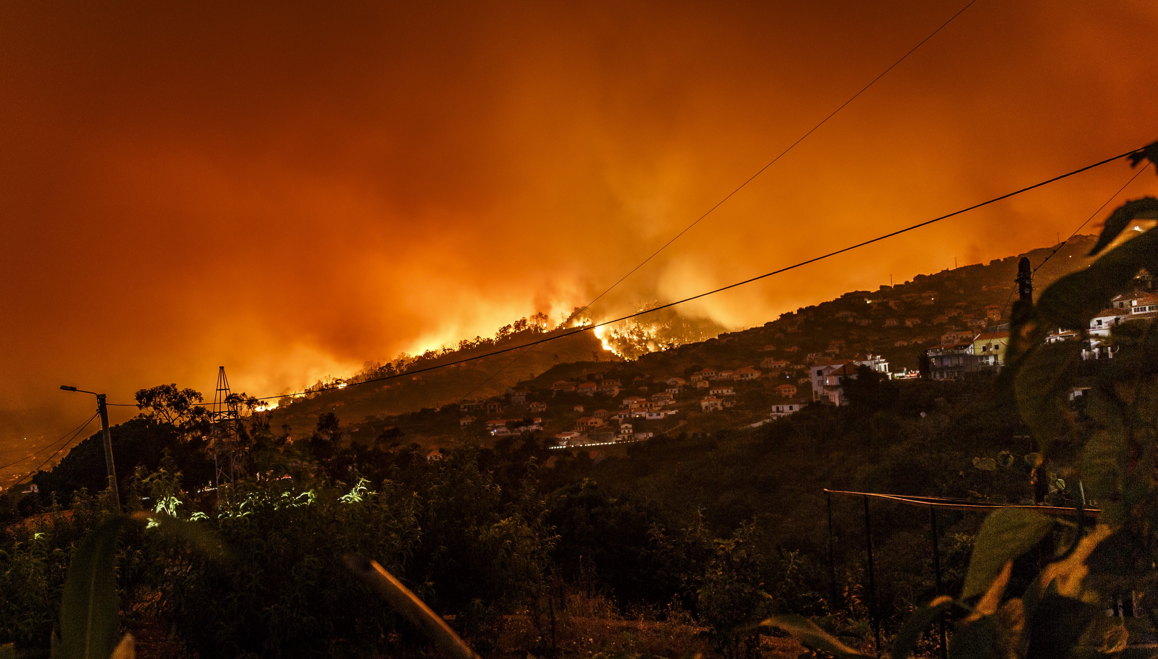 A hillside view on a residential area. There are flames blazing in the background and the sky is red/orange and covered in smoke