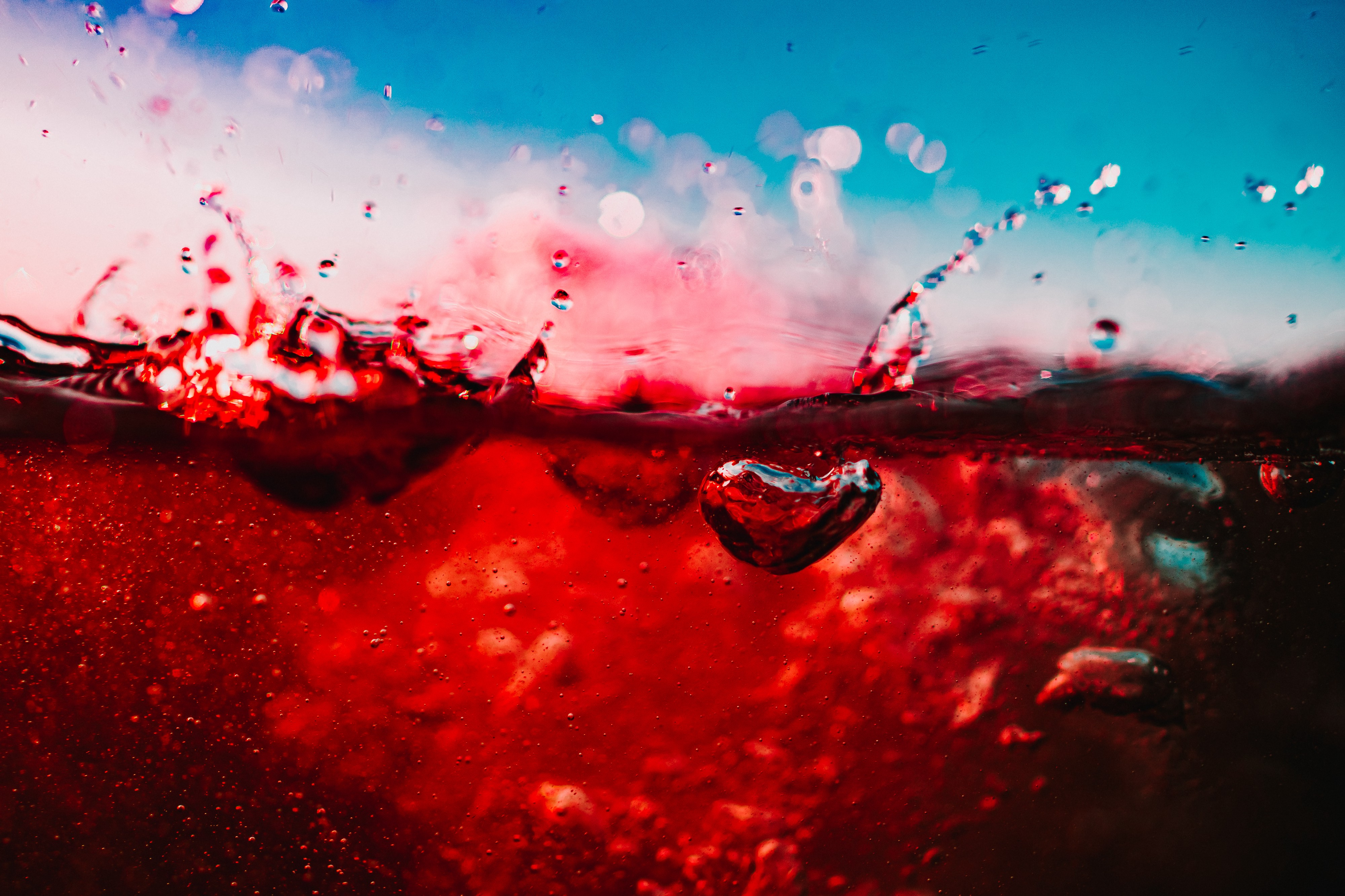 Close up image of bright red wine splashing against a blue background.