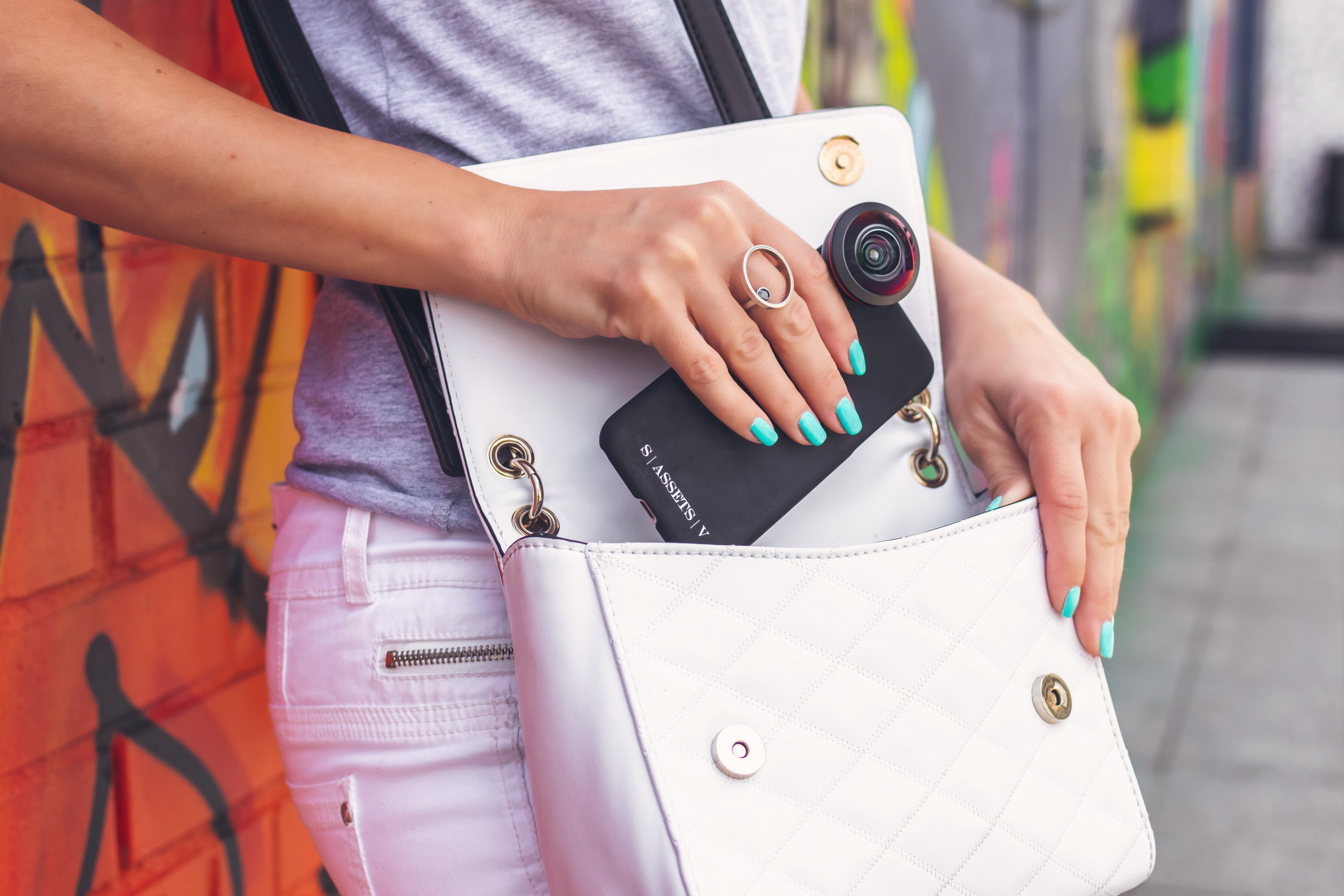 A white handbag is slung across a woman's body. It is open and the woman is slipping her phone into it. She has turquoise nail polish on and behind her is a wall with red and green graffiti.