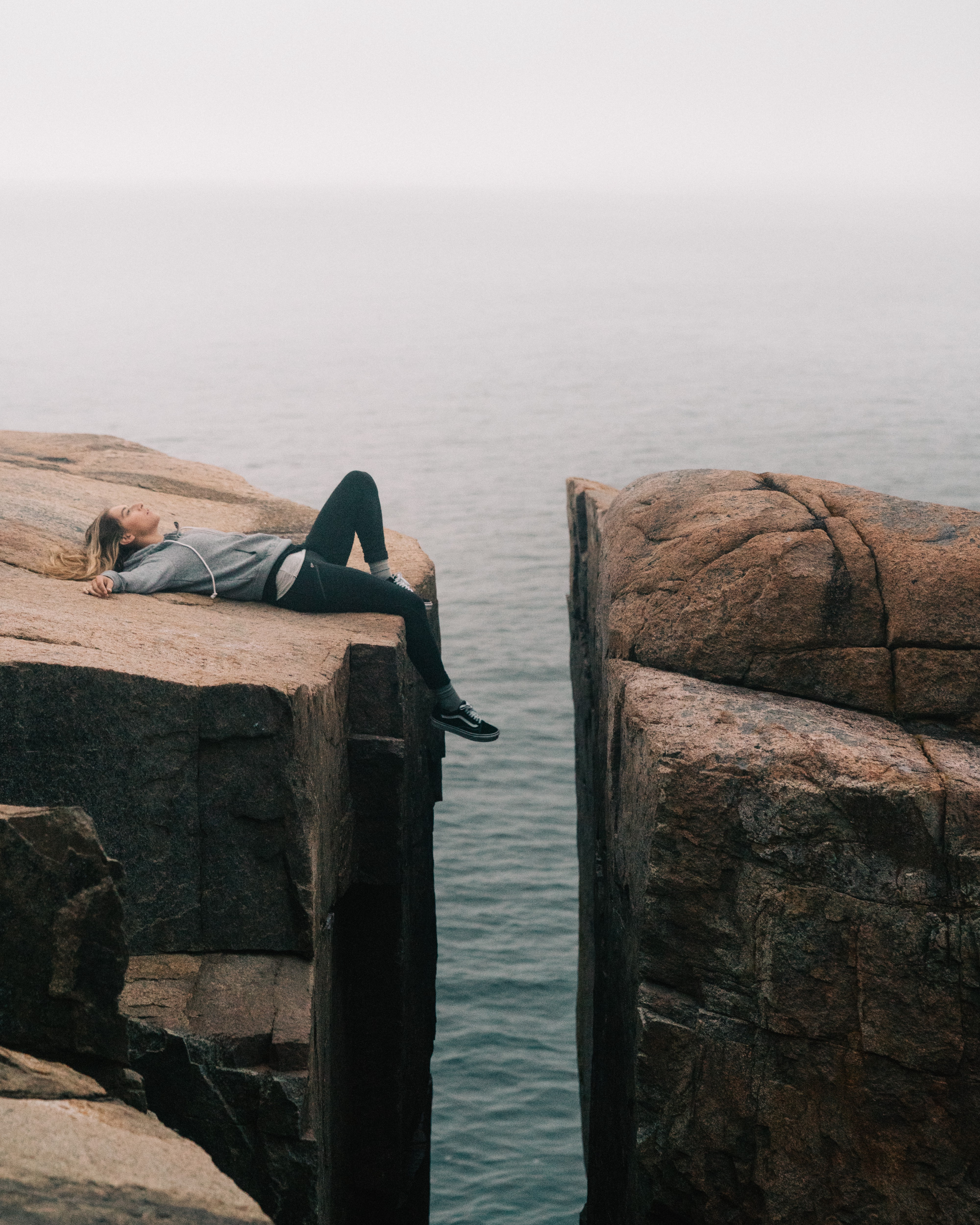 A woman lying down at the edge of a gap between two rocky cliffs